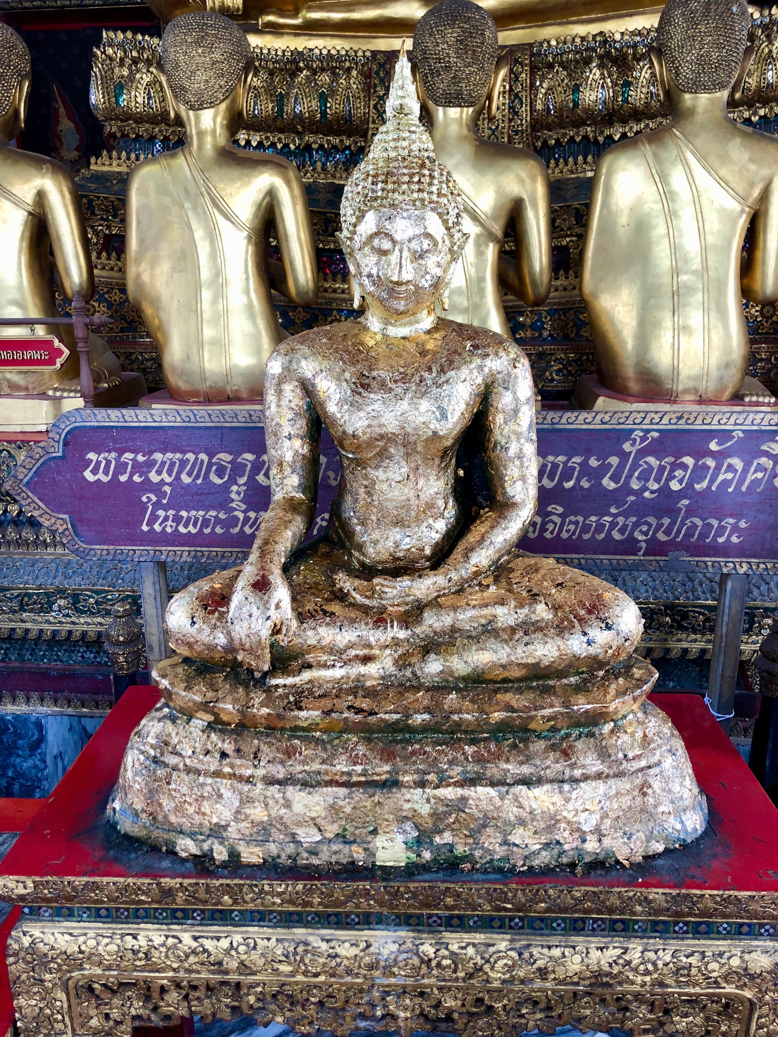 The Buddha's surface is uneven because gold has been pressed onto it by devotees
