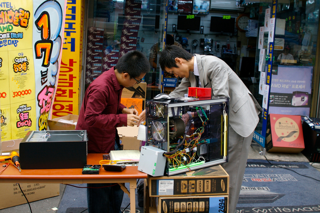 Two guys repairing a computer on an electronic market in Seoul, Korea.