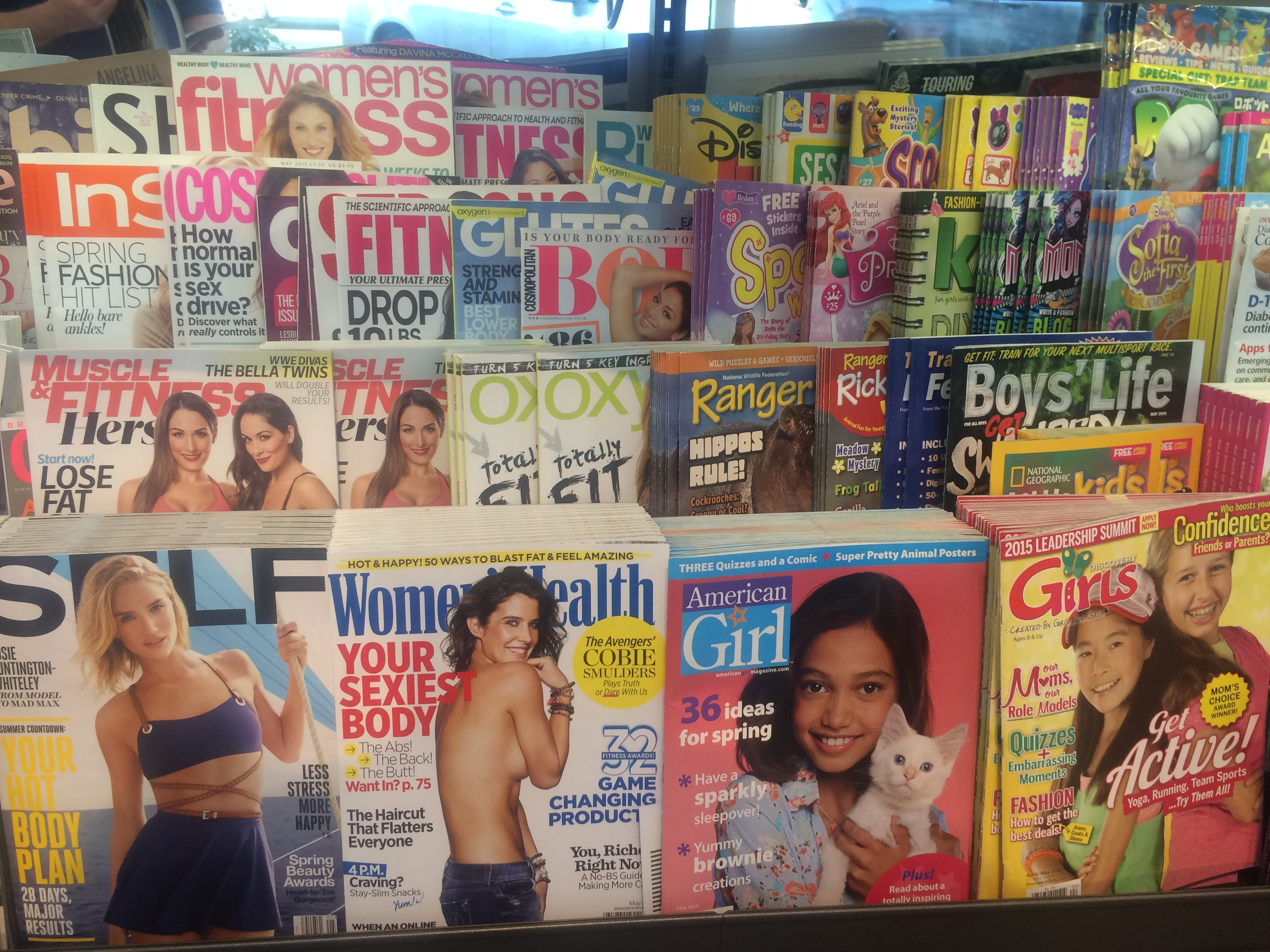 Image: Magazines on display at a Portland, OR bookstore. Women's health and fitness magazines located next to magazines for young girls.