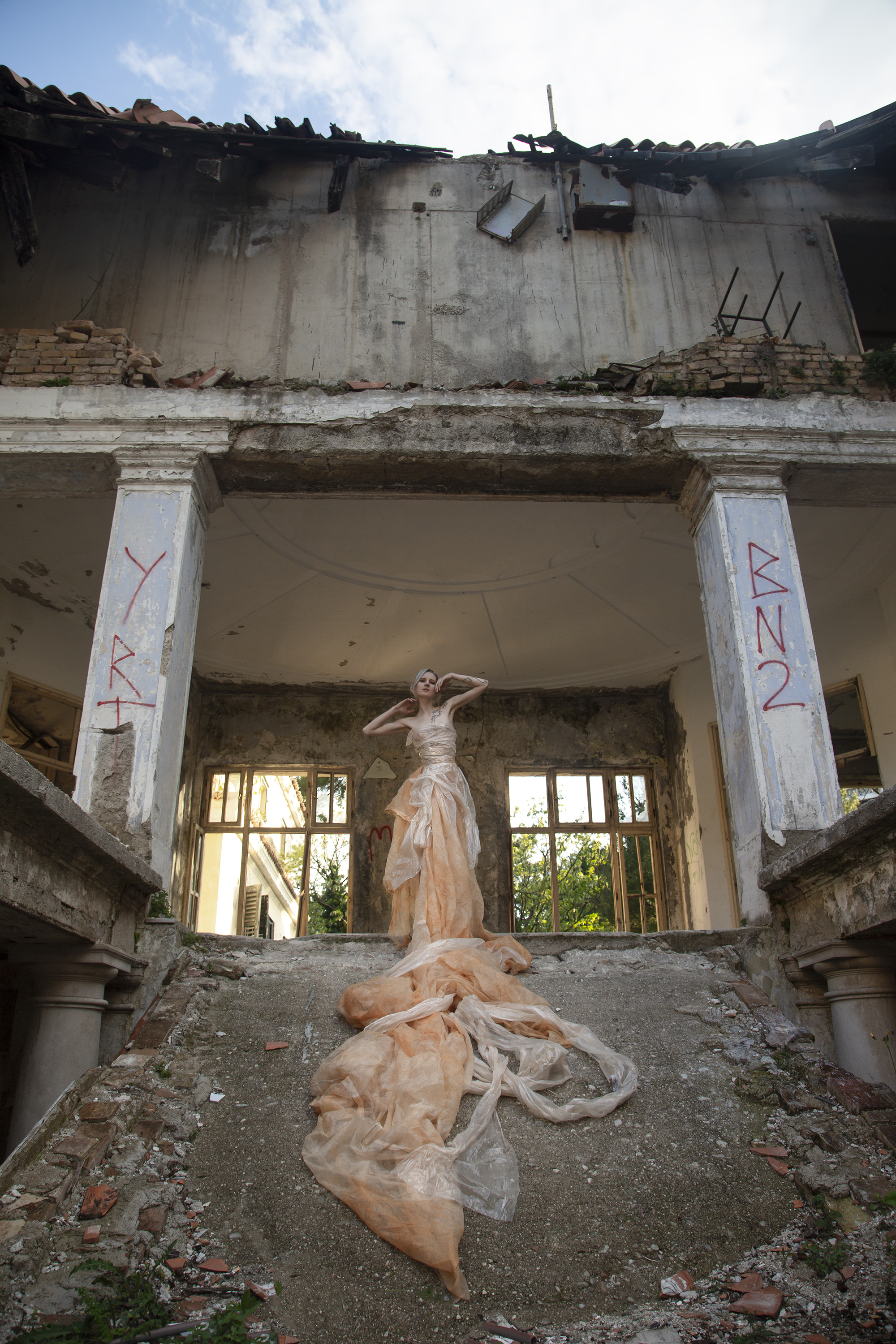Roxx, shot by Redd, at an abandoned hotel in Croatia, wearing a dress draped from discarded mesh and plastic.