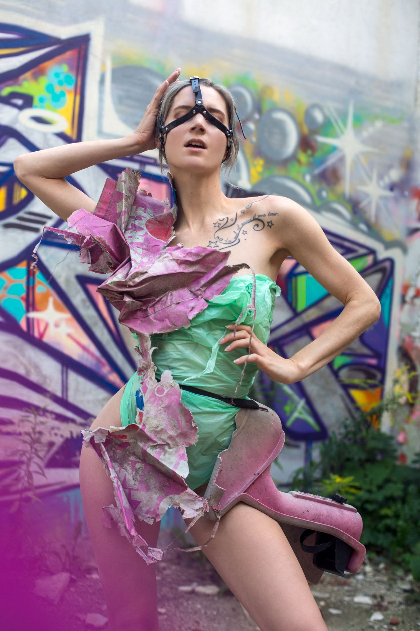 Roxx, shot by Redd, at an abandoned factory in Lodz, Poland, wearing a garment constructed from eco-plastic trash bags, crumbling Pepsi packaging, and a child's safety seat sourced on site.