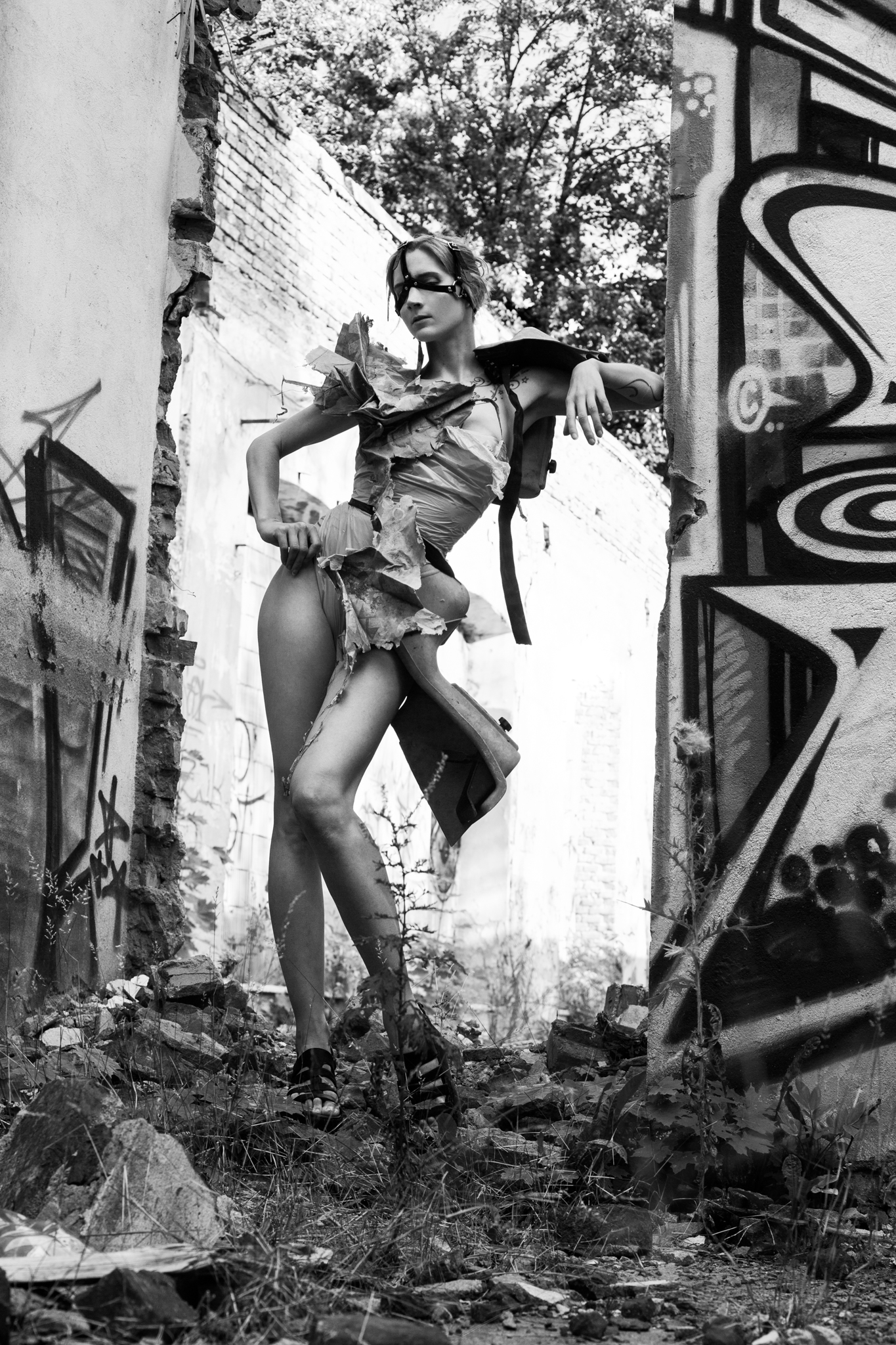 Roxx, shot by Redd, at an abandoned factory in Lodz, Poland, wearing a garment constructed from eco-plastic trash bags, decaying shopping bag, and a child's safety seat sourced on site.