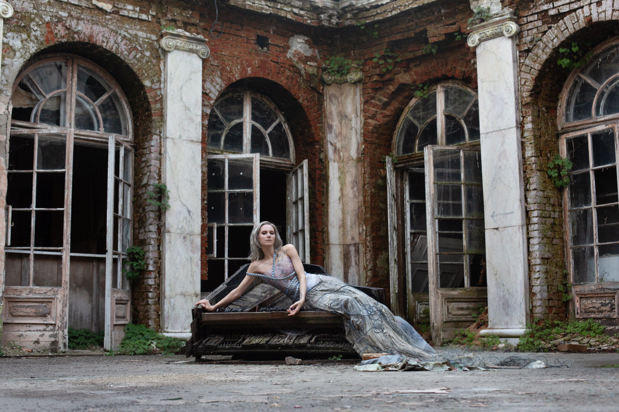 Roxx, shot by Redd, at an abandoned palace in Poland. Wearing a garment constructed from a disintegrating map of Europe (found on site), used fishing net, rubber bath-mat, and recycled belts.