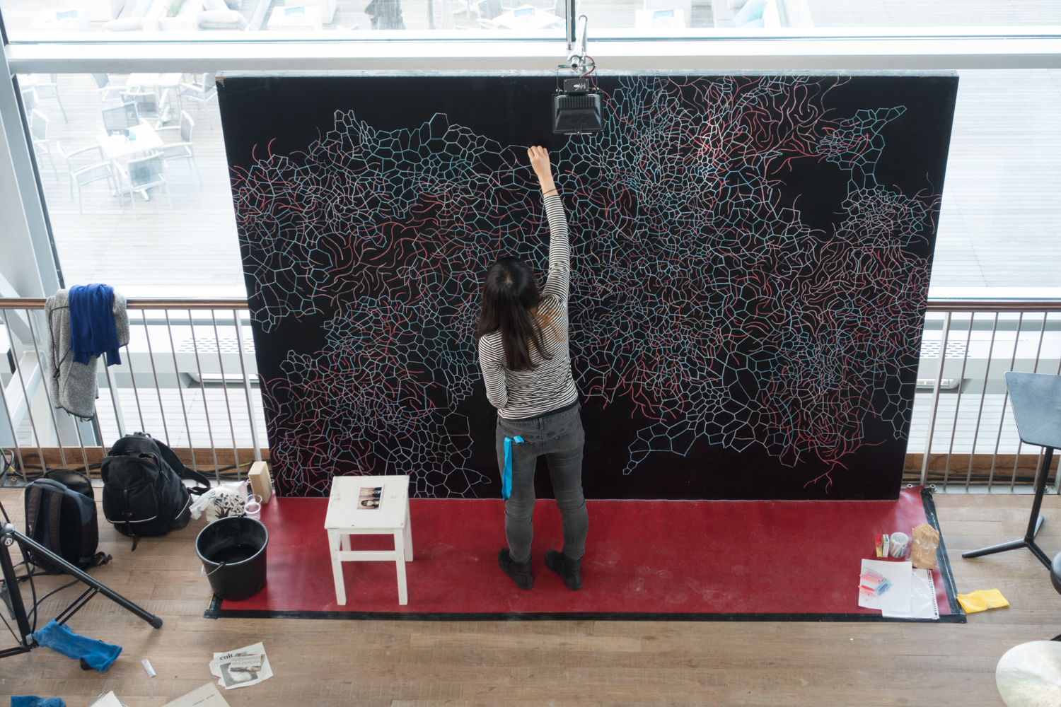 Artist Hanae Shimizu working on her drawing for Urbo Kune at the Muziekgebouw aan 't IJ. Photo by Canan Marasligil