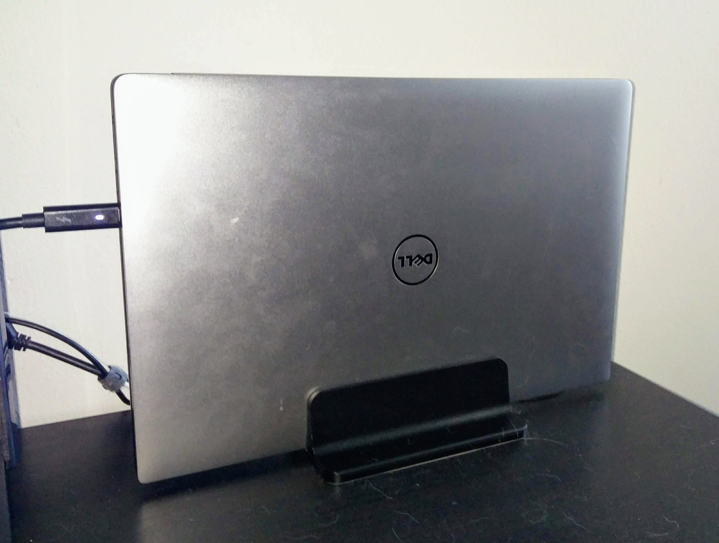 Dell Laptop docked in its stand with a Thunderbolt Connector