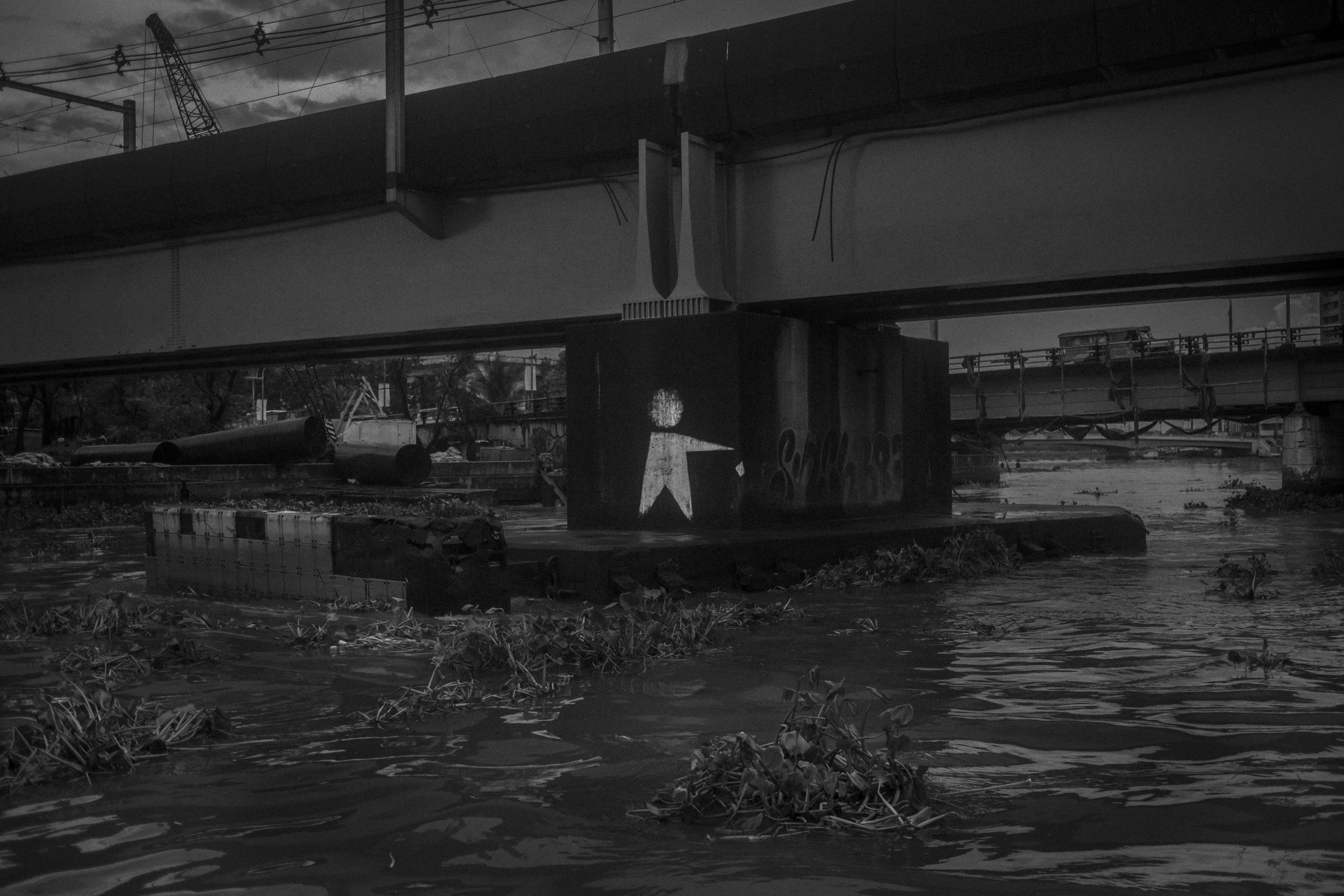 A drawing that alerts to the dumping of garbage on one of the pillars of a bridge over the Pasig River.