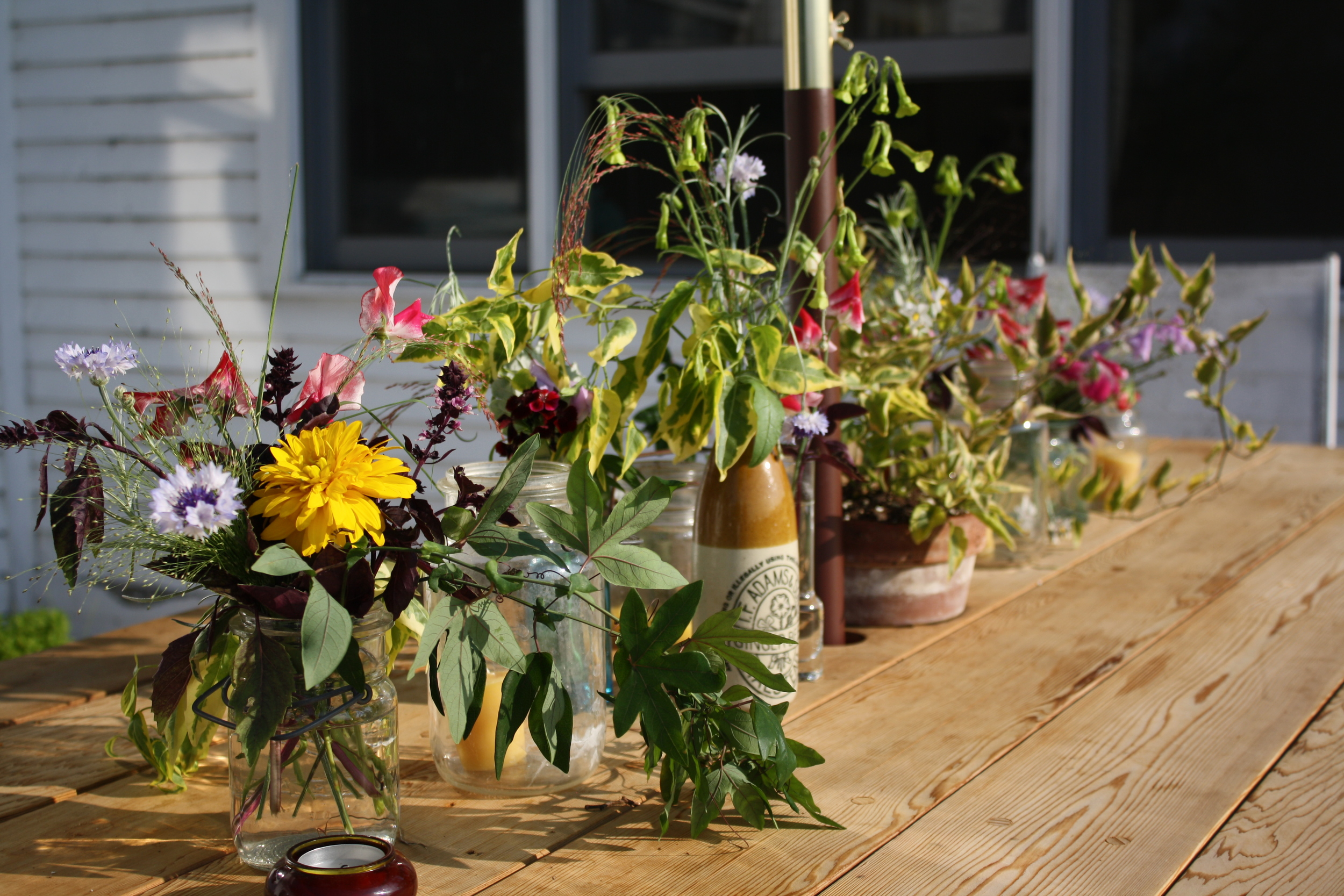 Centerpiece of assorted vases and jars on new outdoor cedar table Adam built...which I've been informed is my birthday and Christmas present for many years to come!