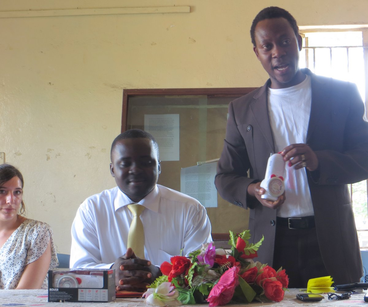 In a donation ceremony at the National Museum in Freetown, ACIPP's Executive Director Simon Tsike-Sossah (standing) discusses radios donated by Ears To Our World. Seated next to Mr. Tsike-Sossah is Ibrahim Tommy, CARL's executive director; seated at far left is Imma Mäder, ACIPP's director for marketing and recruitment. (Photo by Kelsey Lizotte for ACIPP West Africa).