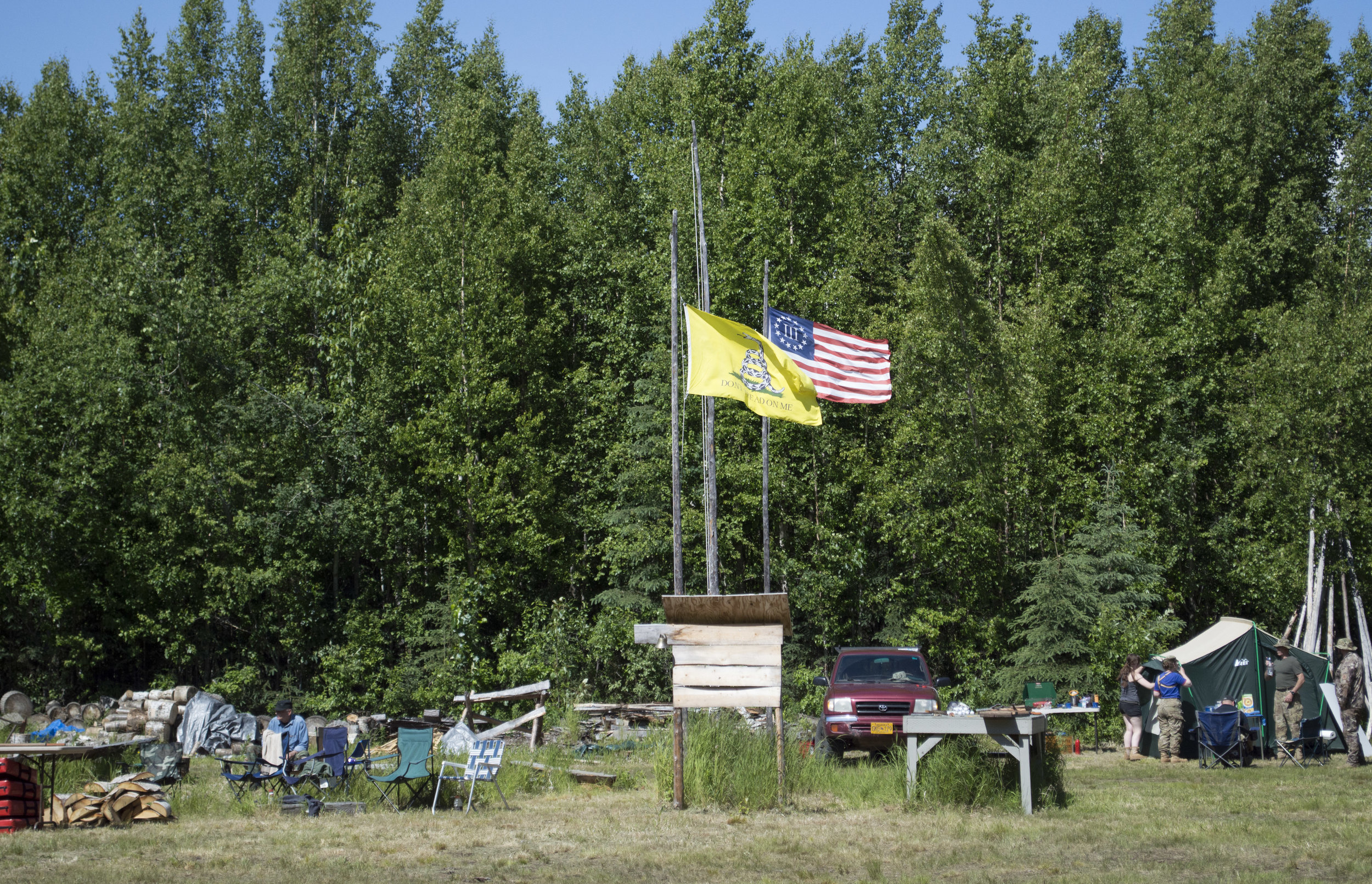 """""""Don't Tread On Me"""" and South Central Patriots' flags by the community campfire."""