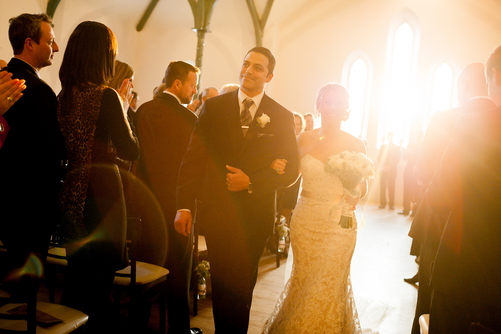 Bride and groom walk down the isle after their wedding ceremony at the Enoch Turner Schoolhouse in Toronto.