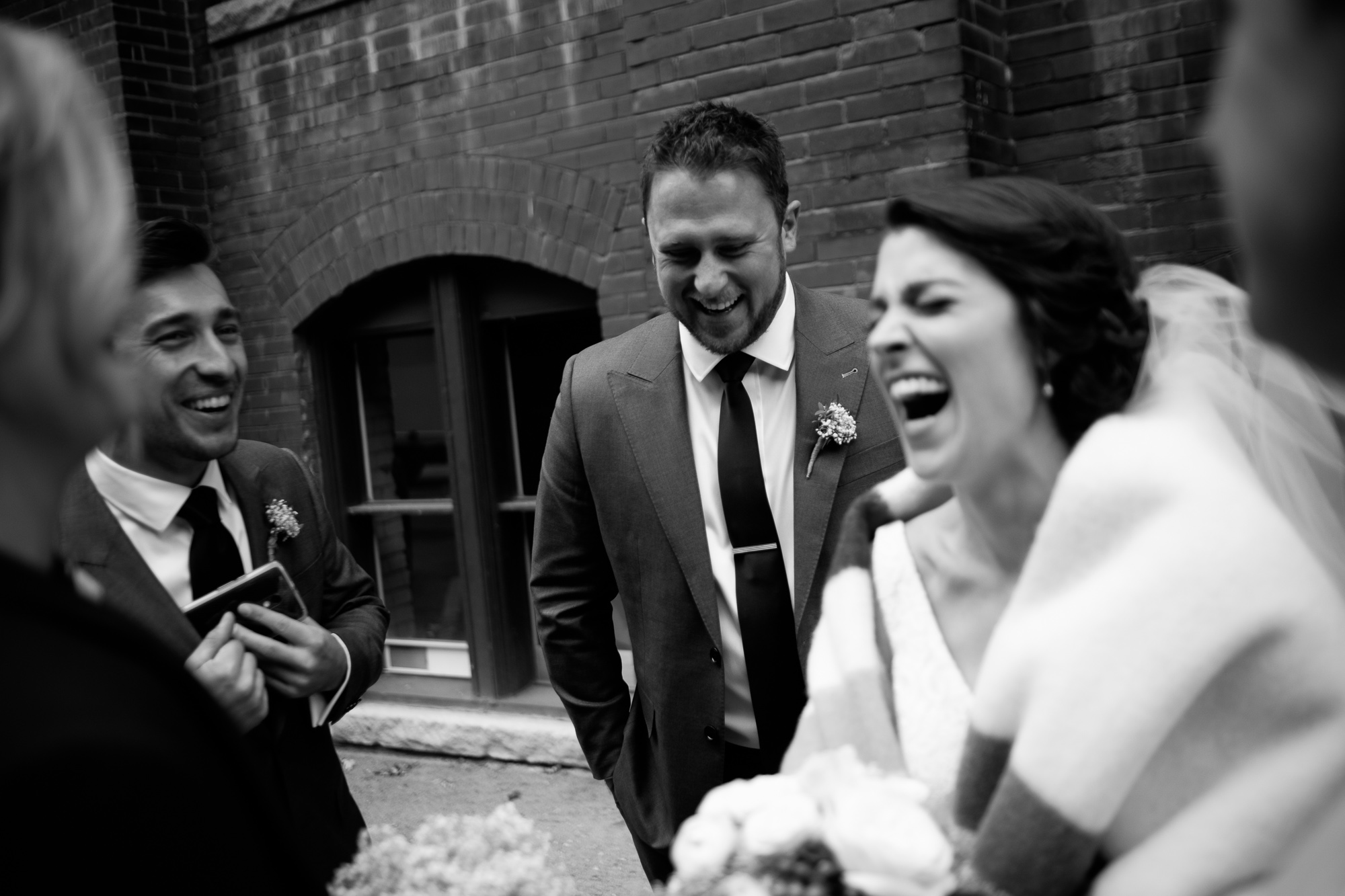 The bridal party enjoys a laugh while we photograph the wedding party portraits in Toronto's Liberty Village.