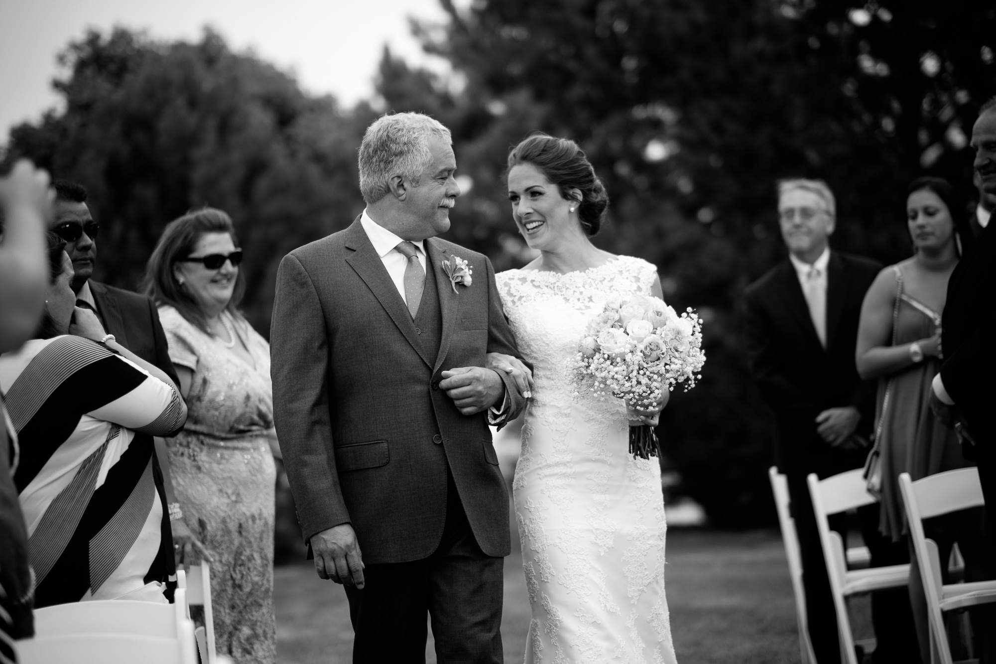 Rebecca and her father share a moment as they walk down the aisle during their outdoor wedding ceremony at the Hessenland Inn.