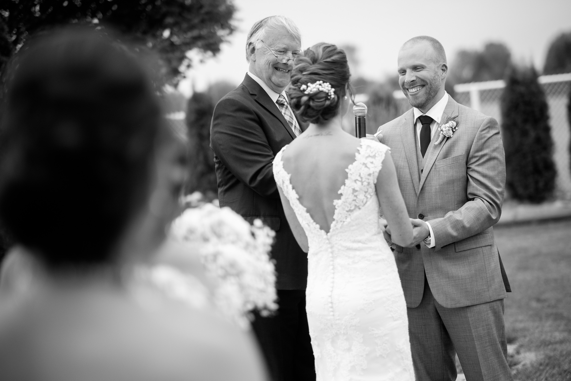 Rebecca + Jeff laugh as they exchange vows during their wedding ceremony at the Hessenland Inn.