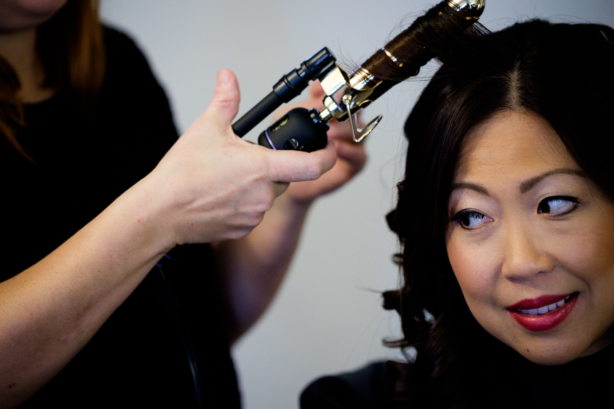 A bridesmaid has her hair done before the wedding.