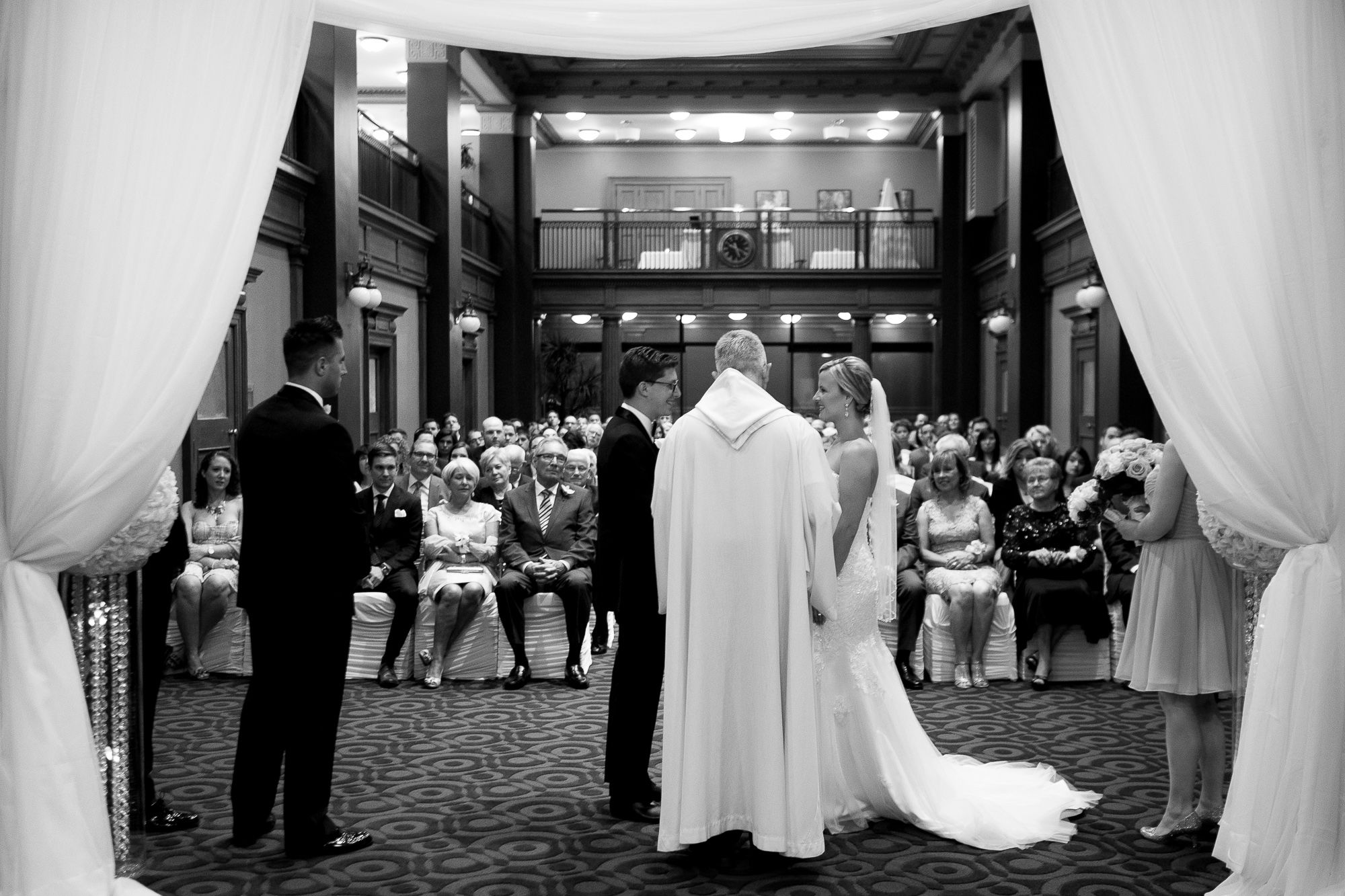 Danielle + Eric exchange their wedding vows as the guests look on during their ceremony at One King West Hotel In Toronto.