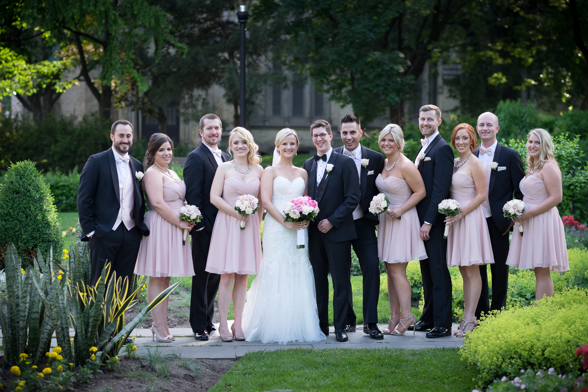 Danielle and Eric pose with for a portrait with their wedding party at a park in downtown Toronto.