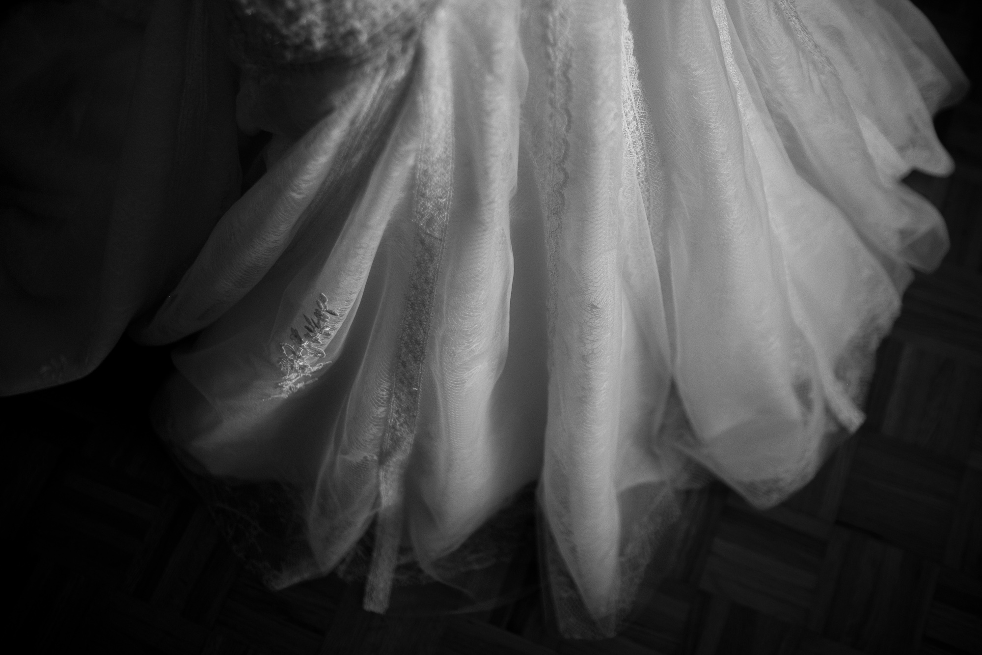 A black and white detail shot of Olivia's wedding dress from her wedding at Copper Creek Golf Course.