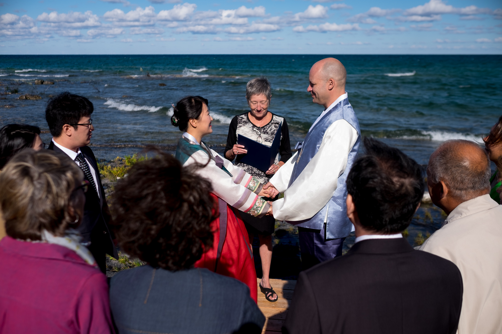 Guests look on as Joohee + Joel are married on the shore of Georgian Bay in Tobermory.