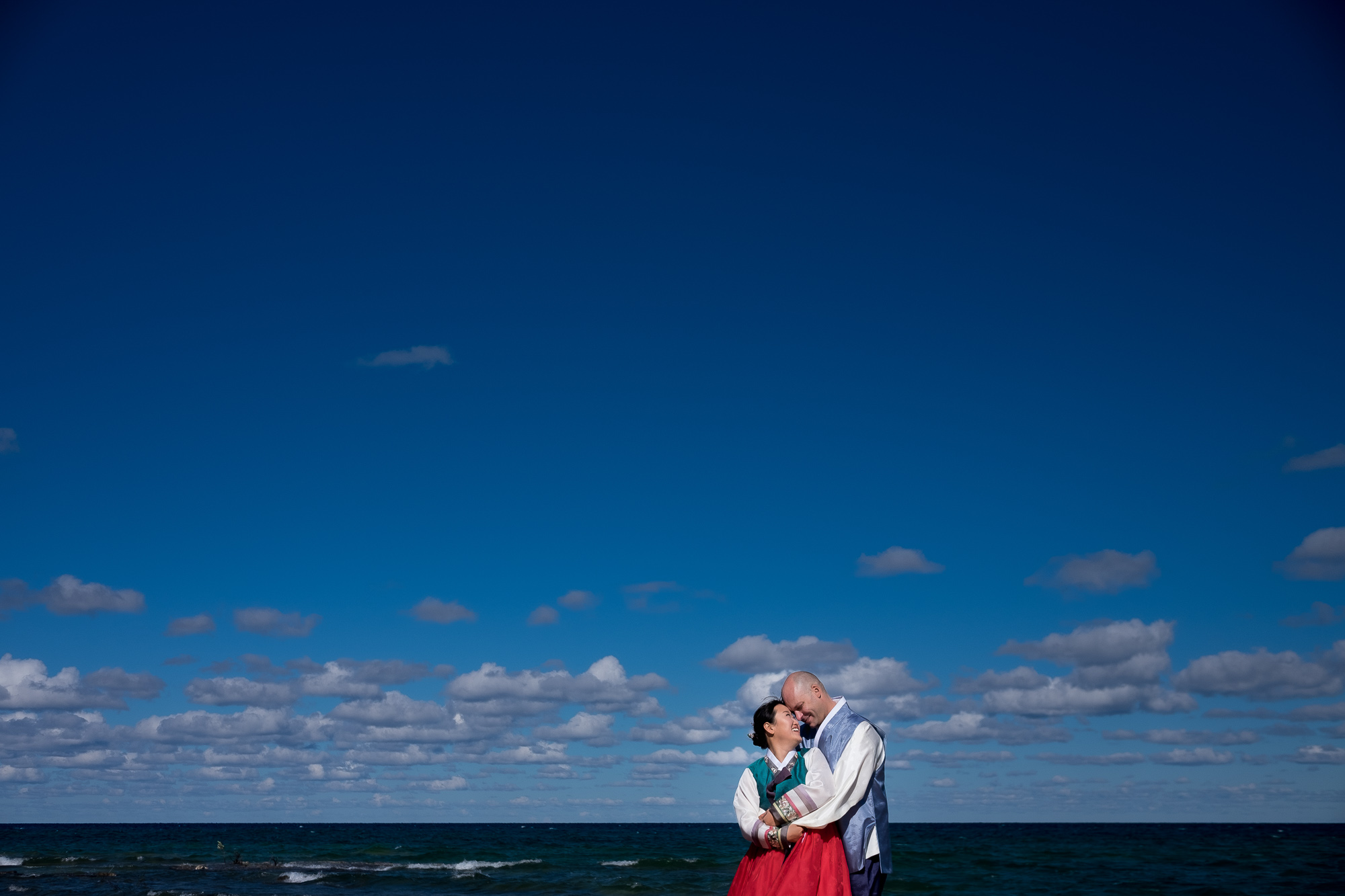 A wedding portrait of Joohee + Joel wearing their traditional Korean wedding attire on the waterfront in Tobermory.