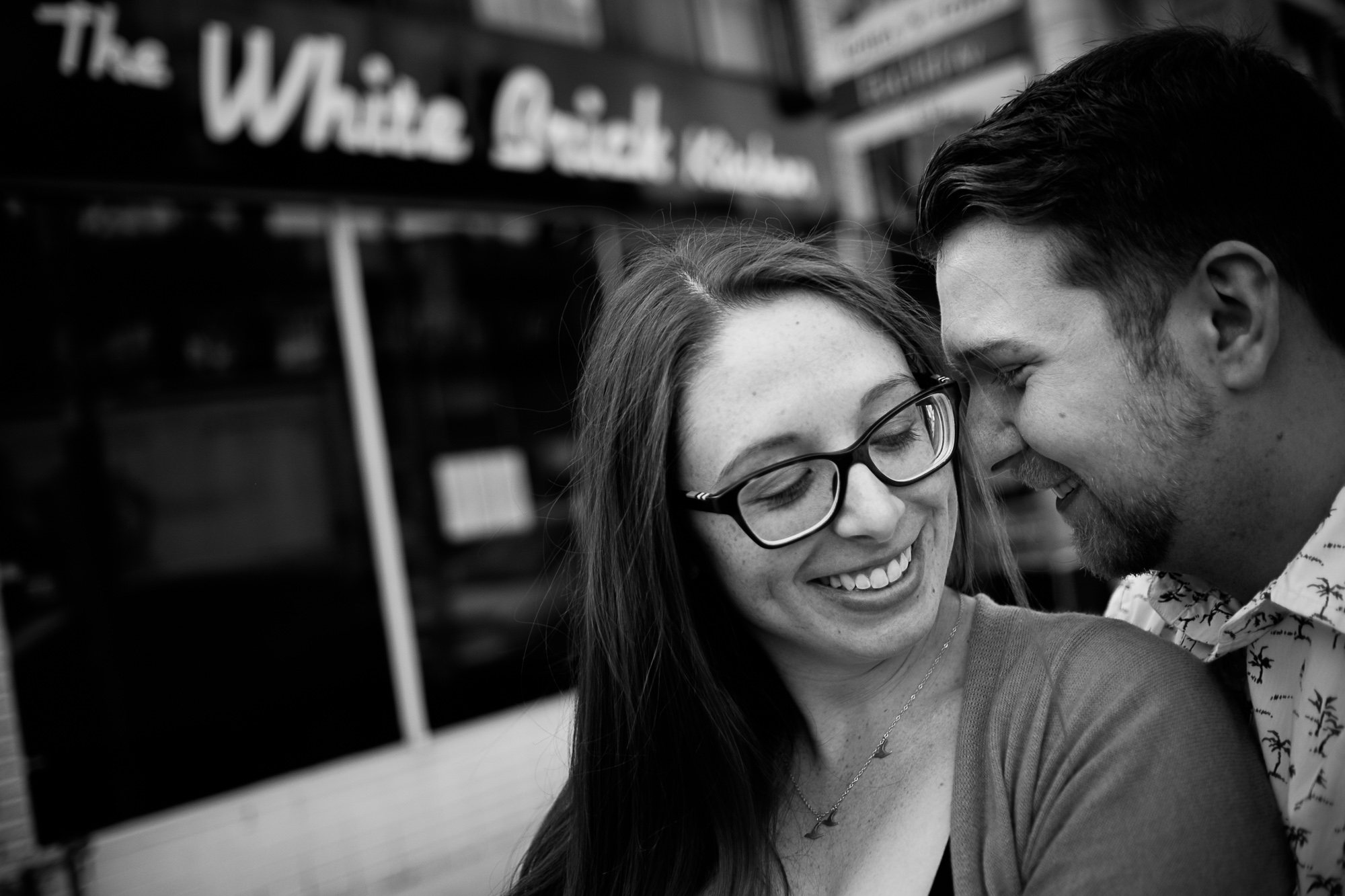 Haley and Stephen pose for an engagement portrait during their engagement session at the restaurant they own in Downtown Toronto.