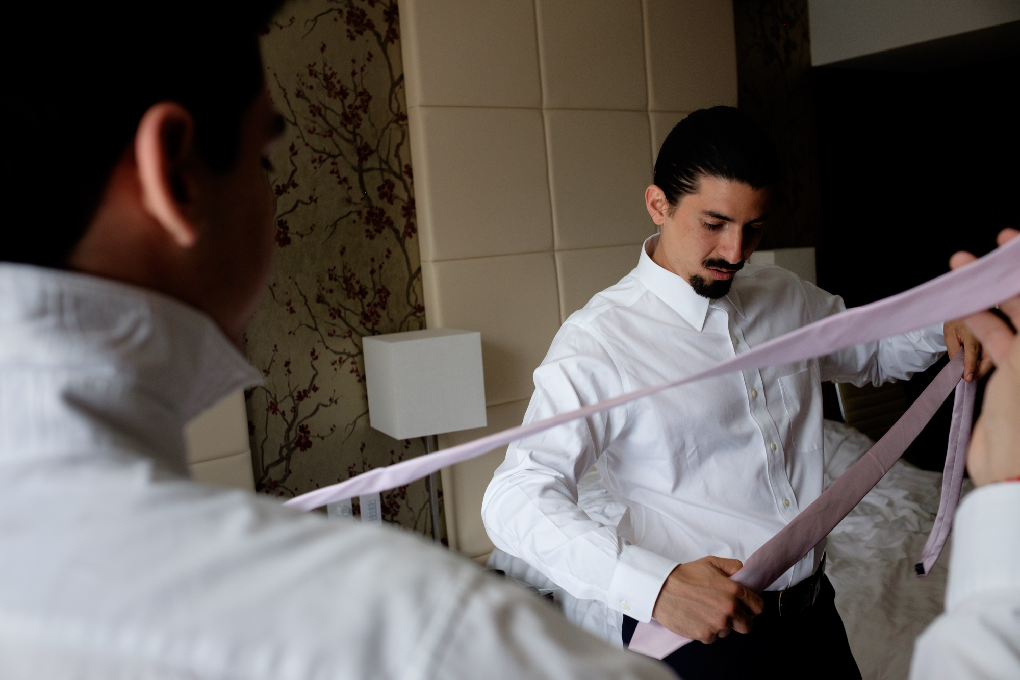 Felipe and his groomsmen get ready and adjust their ties in their suite at the shangri-La Hotel in Toronto before their wedding at the Fermenting Cellar.