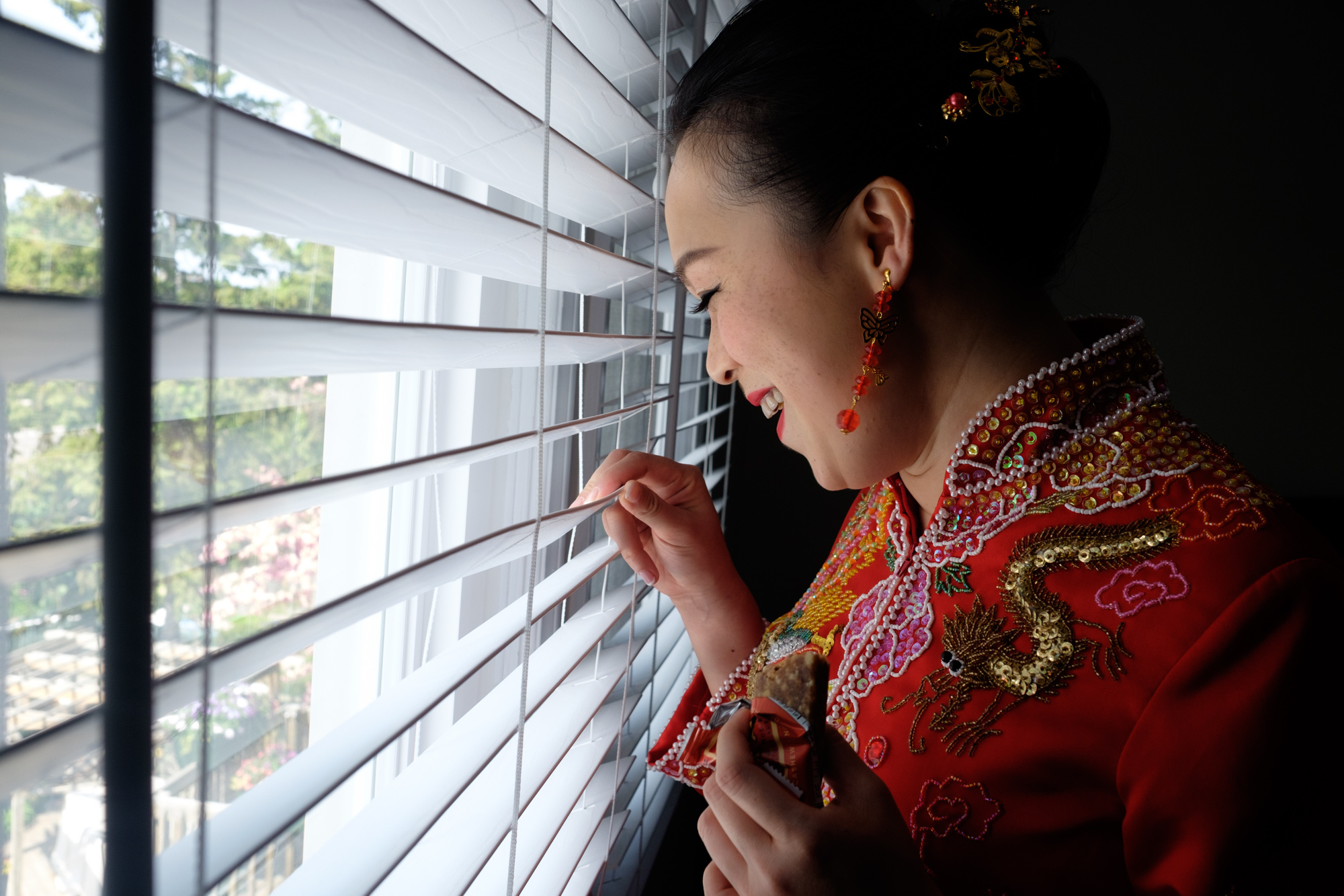 Jing, wearing traditional chinese attire, sneaks a view of guests arriving before her at her wedding ceremony.