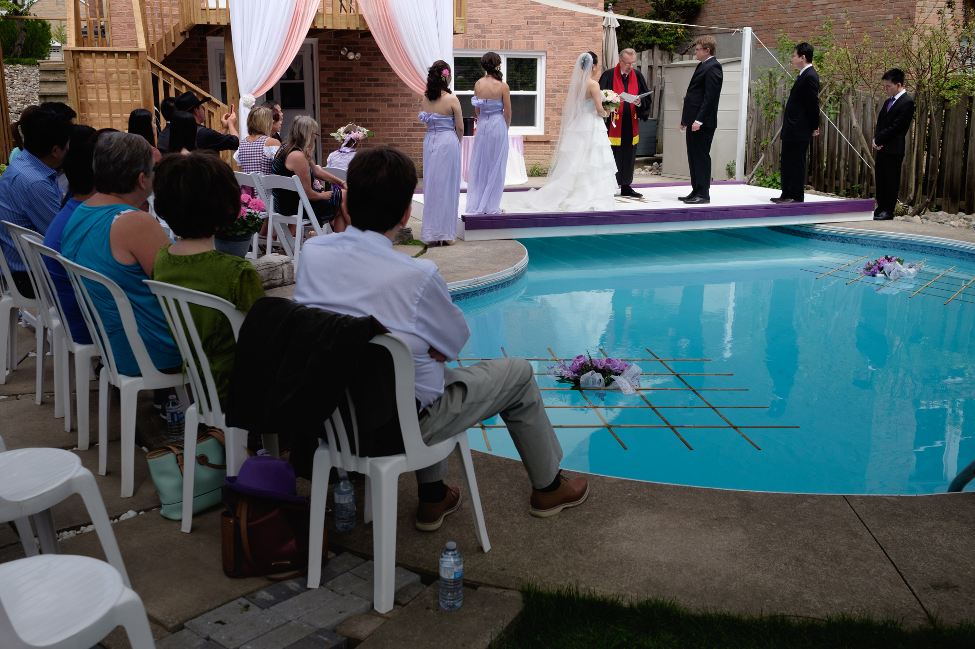 A photograph of Jing + Rene's outdoor wedding ceremony on a platform over their parents backyard pool.