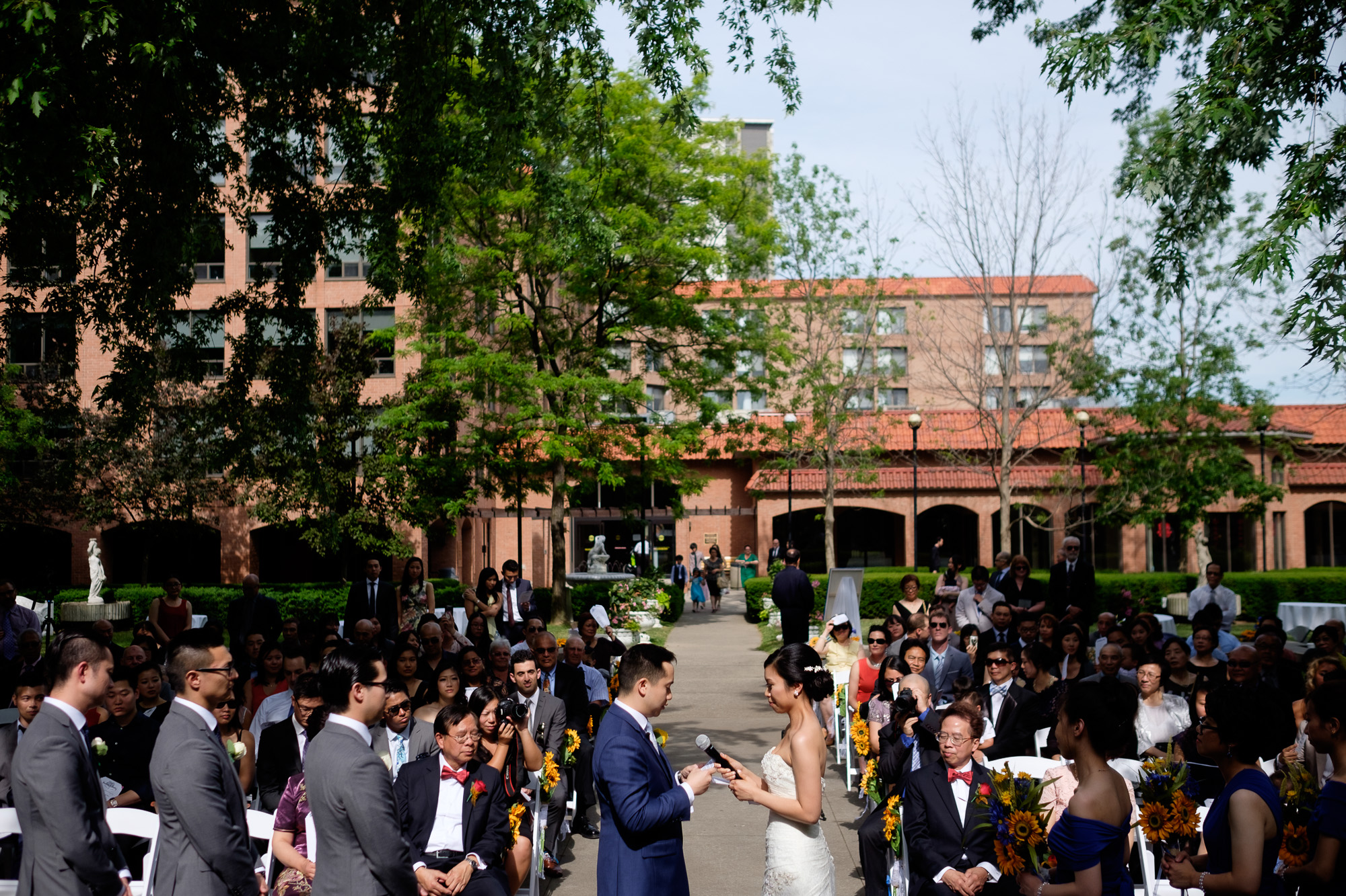 Sherry + jonathan exchange wedding vows during their outdoor wedding ceremony at the Columbus Centre in Toronto.