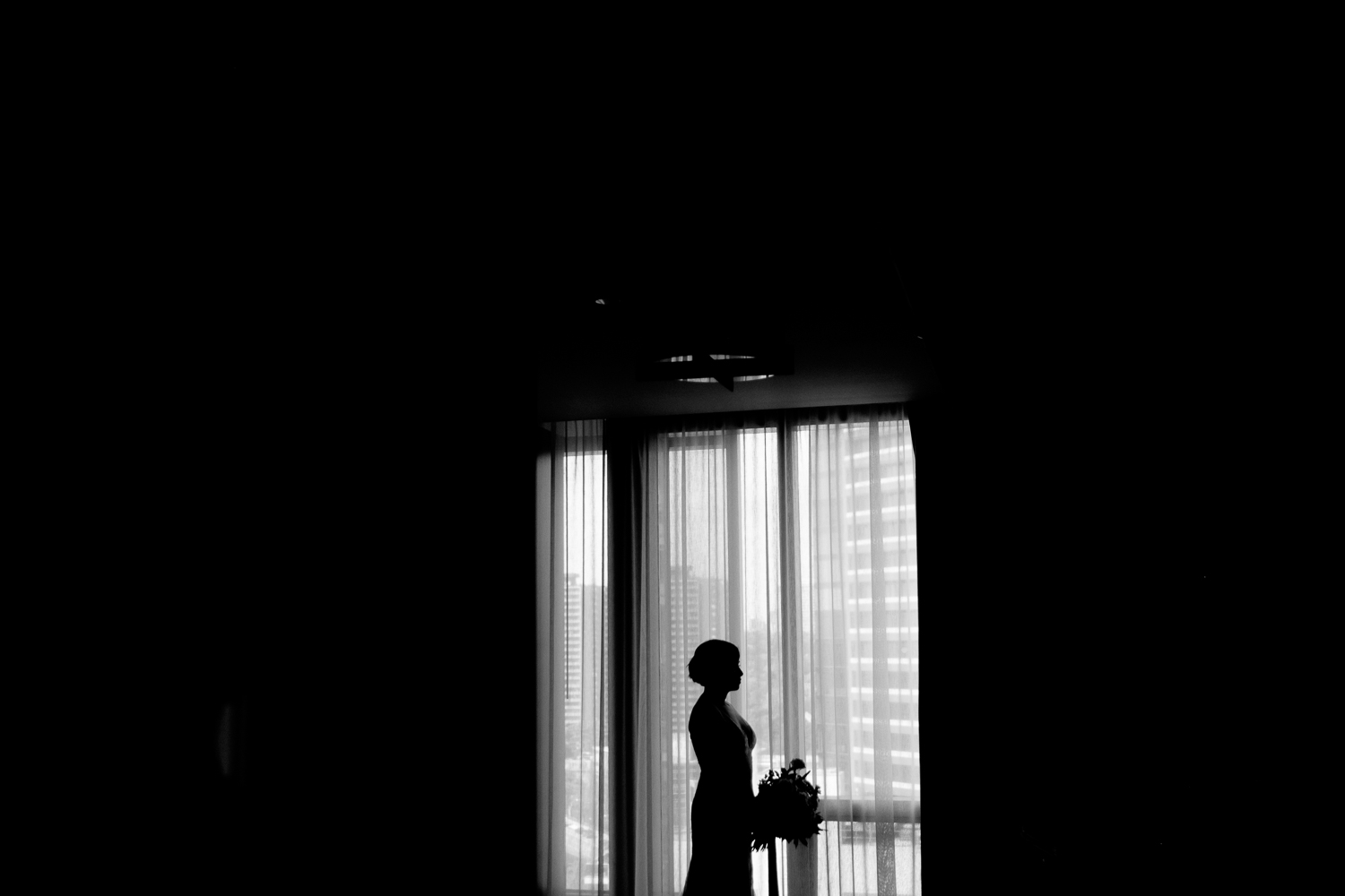 A silhouette wedding portrait of the bride in her suite at the Four Seasons hotel in Toronto.