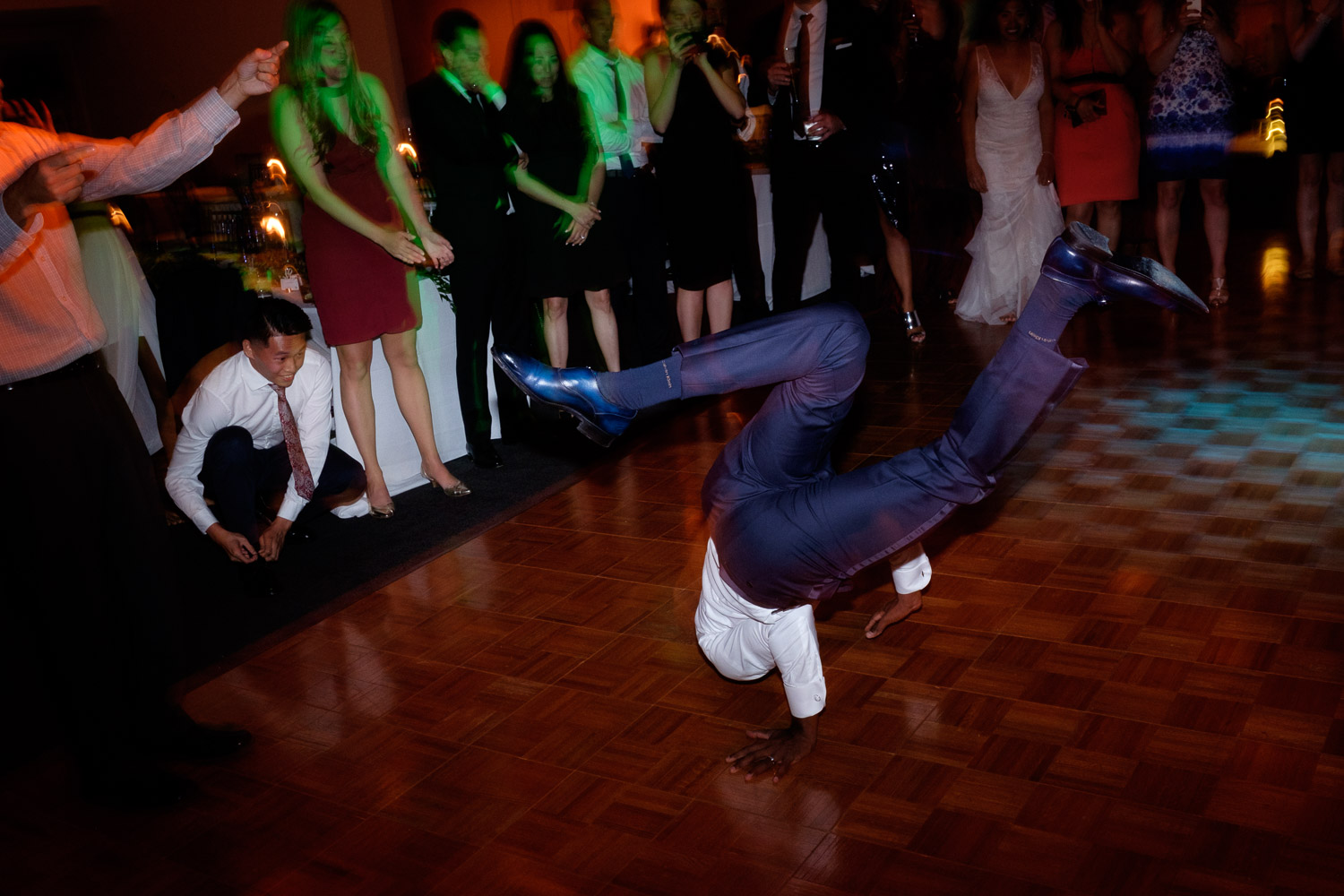 The groom does some breakdancing on the dance floor during his wedding reception at the Art Gallery of Ontario in Toronto.