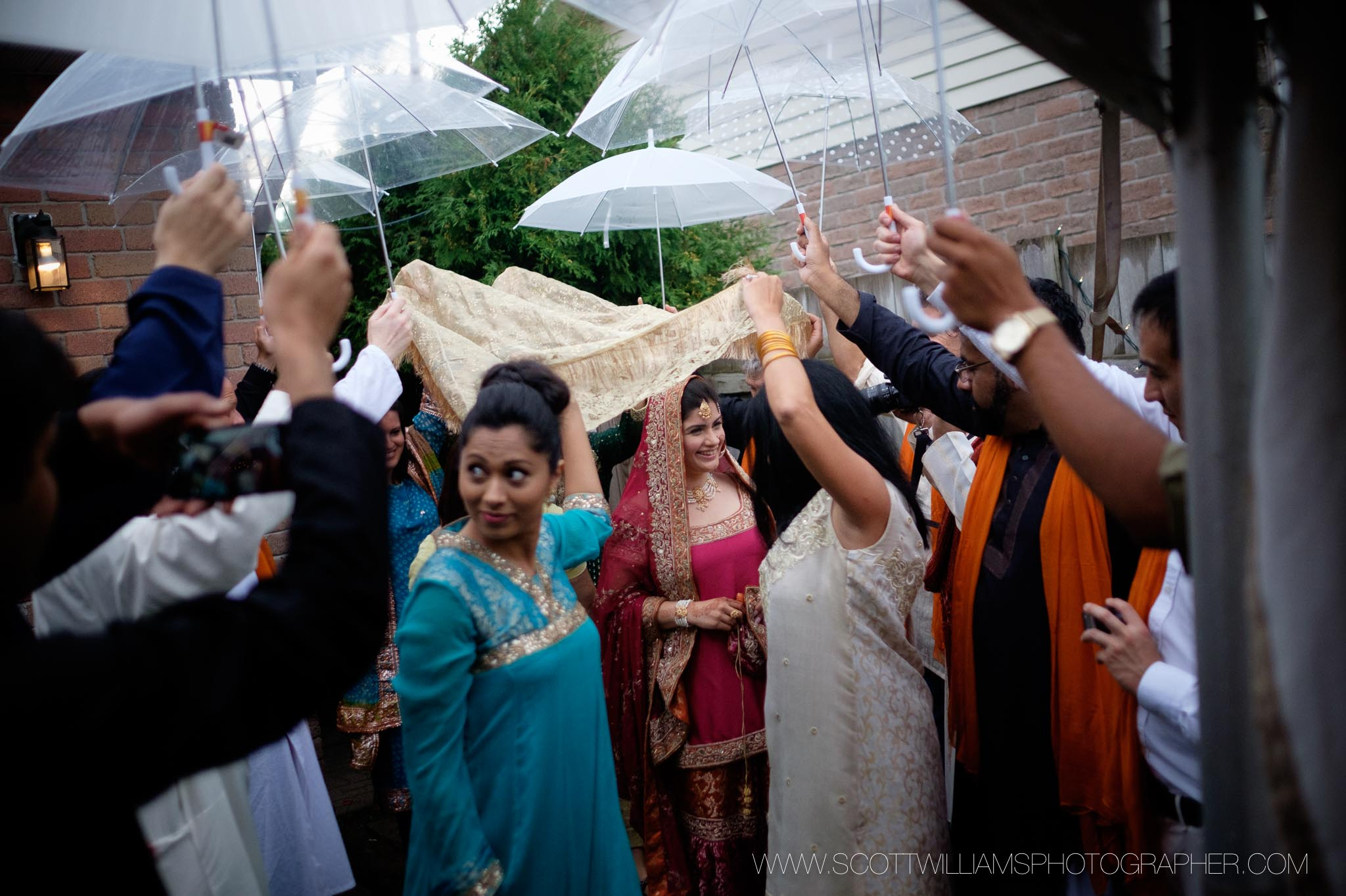 The bride makes her entrance to their backyard wedding ceremony on a rainy day.