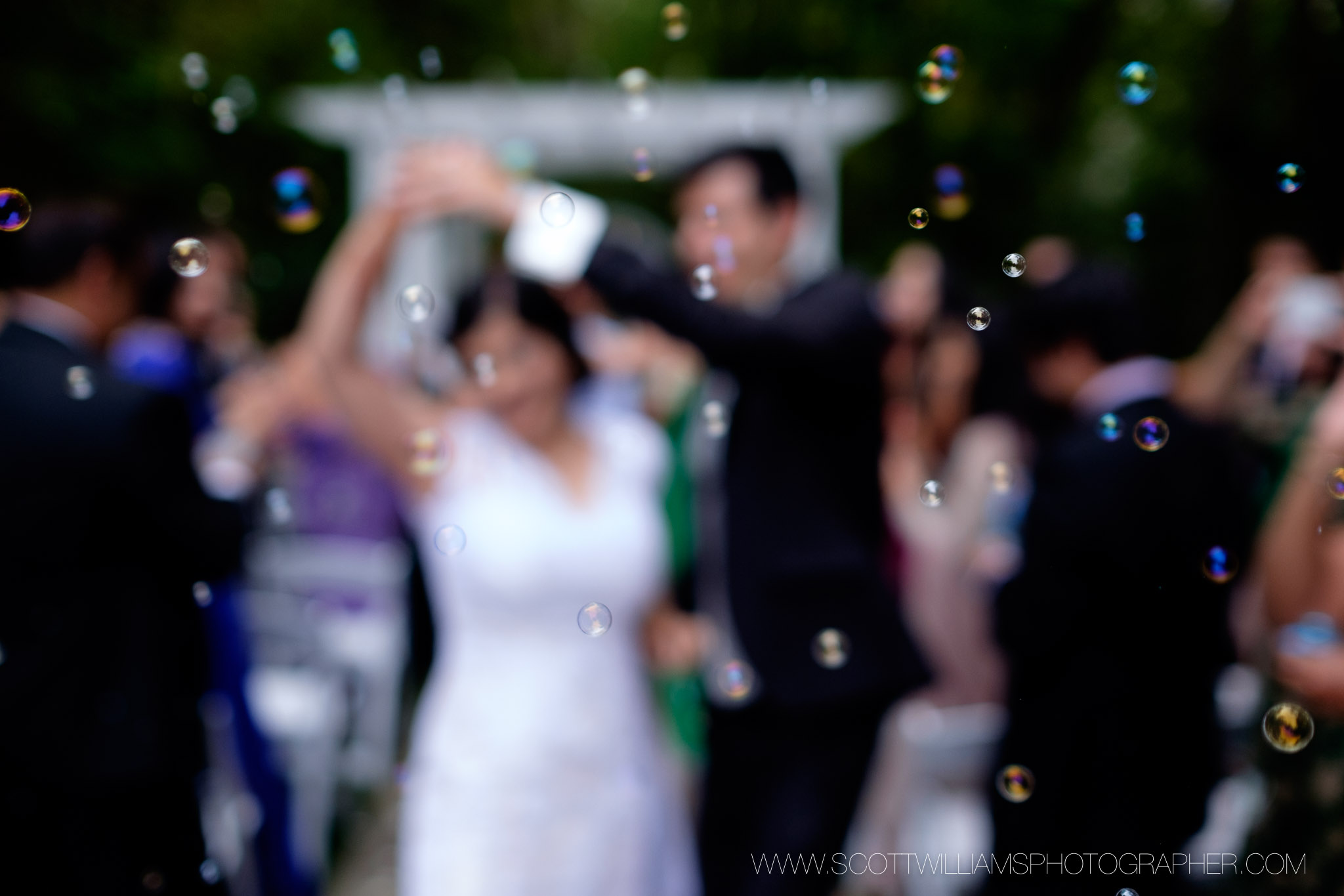 Guests blow bubbles as the bride and groom dance their way up the aisle after their outdoor wedding ceremony at the Ancaster Mill in Ancaster, Ontario.
