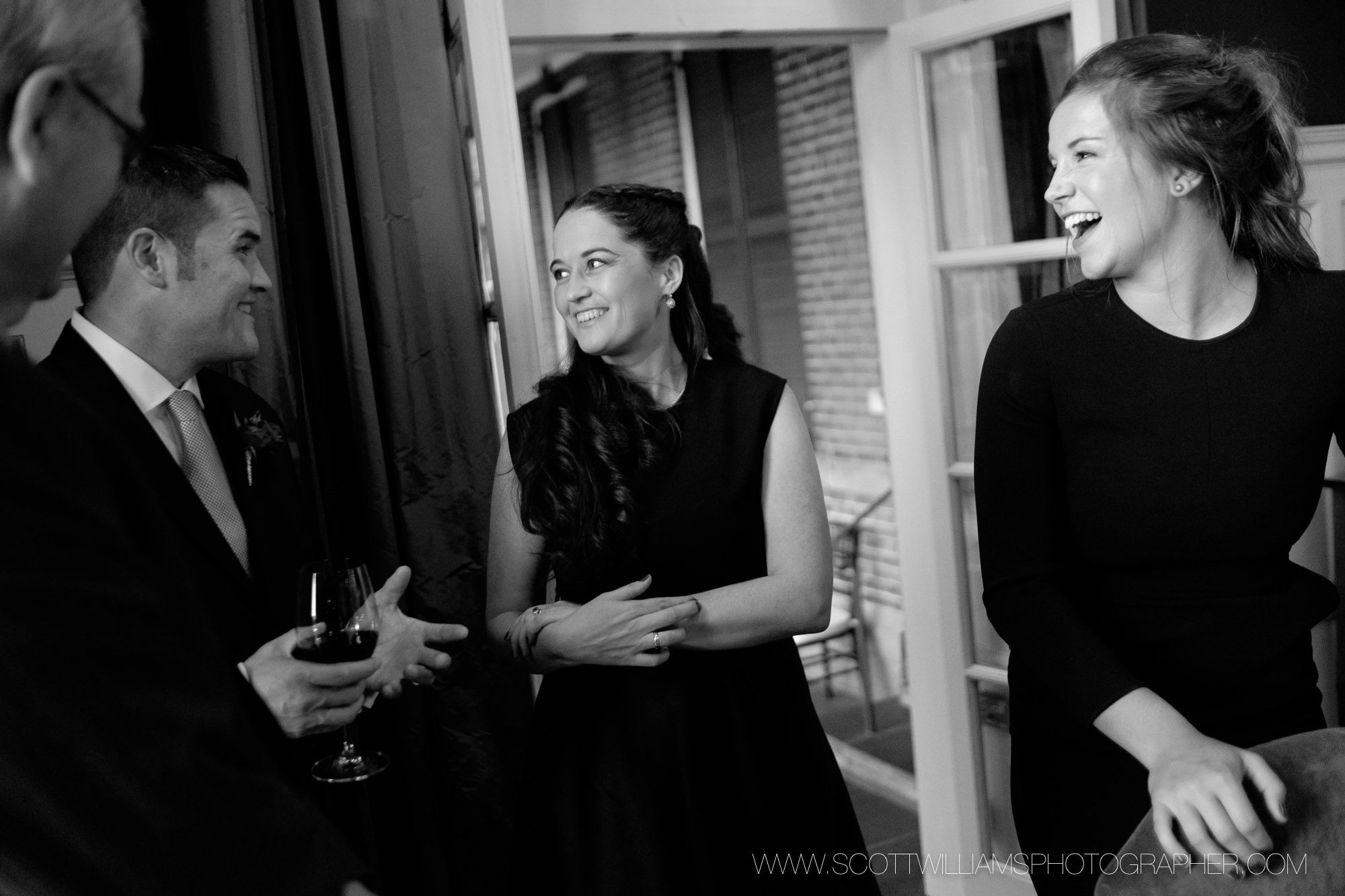 A candid black and white photograph of guests at a small, intimate wedding at Langdon Hall in Cambridge, Ontario.