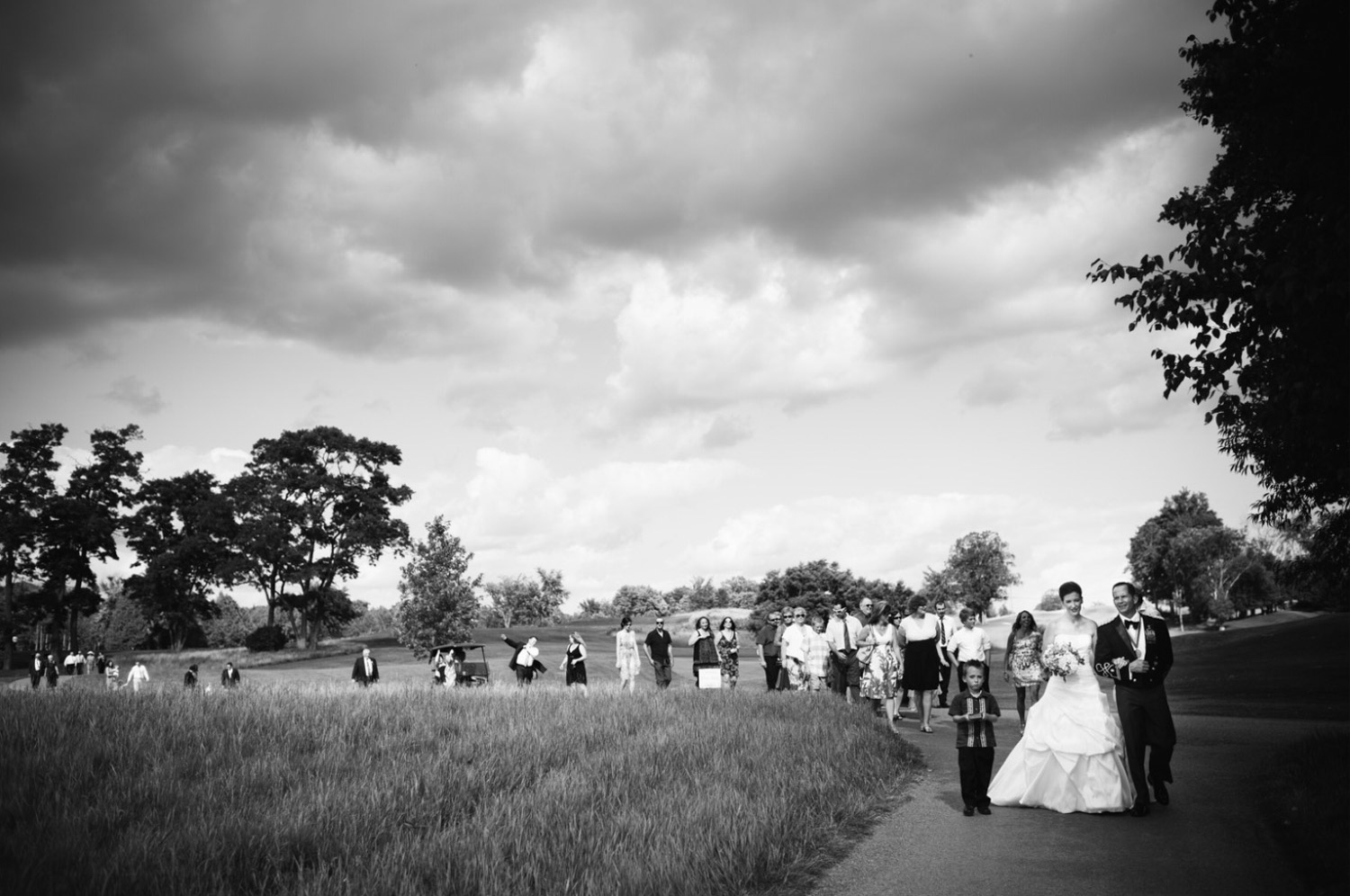 I love this image from Deborah & Joe's wedding at Wildfire Golf Club on the shores of Stoney Lake in the Kawartha region of Ontario.    We had just finished their outdoor wedding ceremony in the ruins of an old barn and Deborah + Joe were leading all their guests back to the reception.  Usually, after a ceremony it's a bit of controlled chaos as everyone is lining up to get out of the church and then getting into limo's and cars to head to the reception but here it was just a nice moment as everyone walked back and enjoyed the beautful day.
