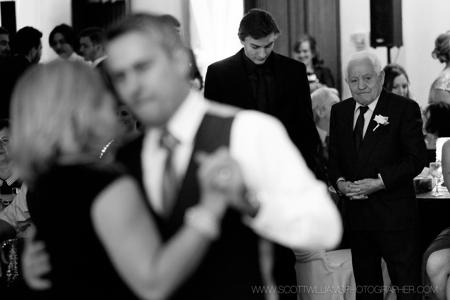 The grooms father looks on as David dances with his sister during their wedding reception in North Bay, Ontario.