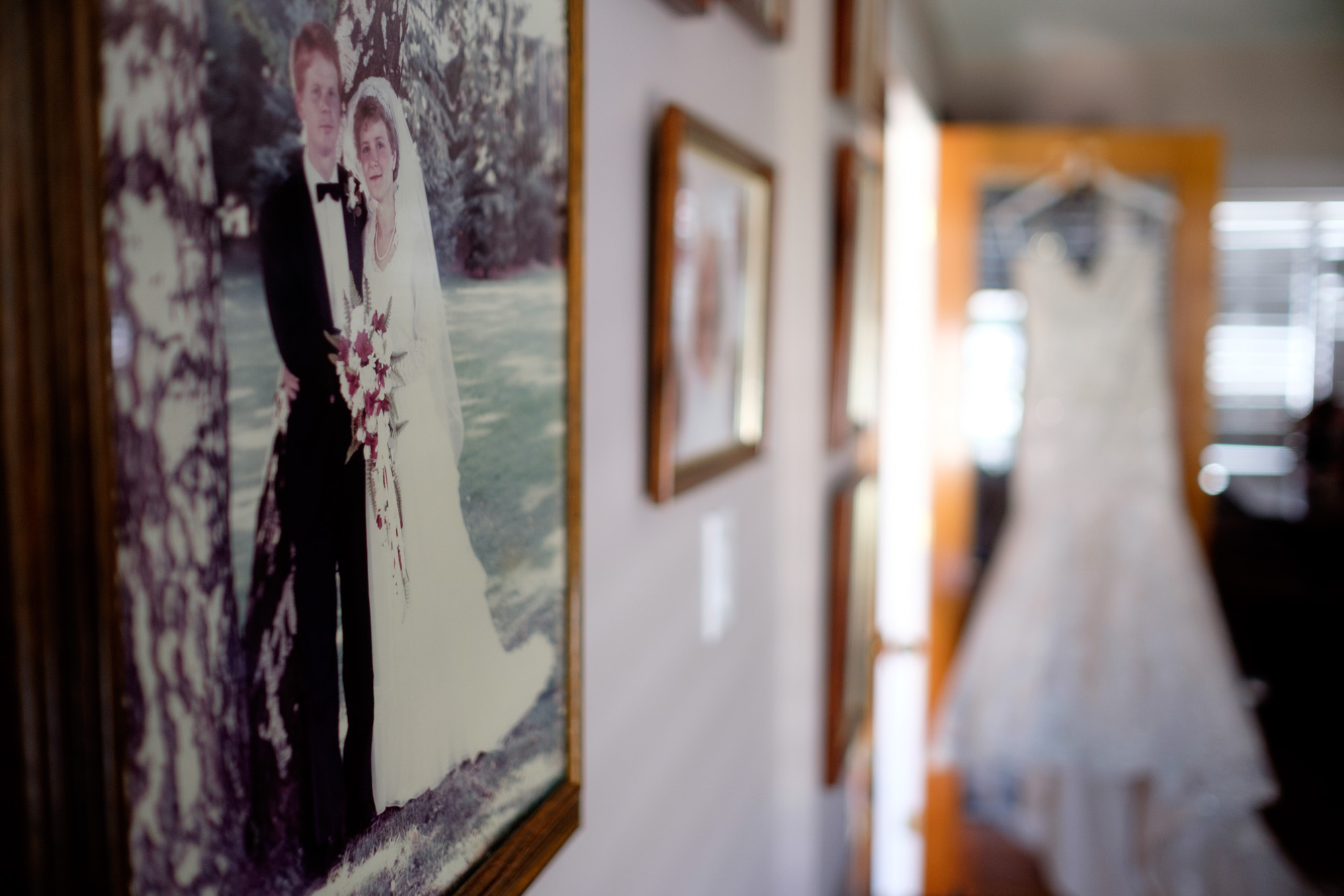 The brides wedding dress hangs in her parents home before the wedding ceremony in Cambridge at Whistle Bear.