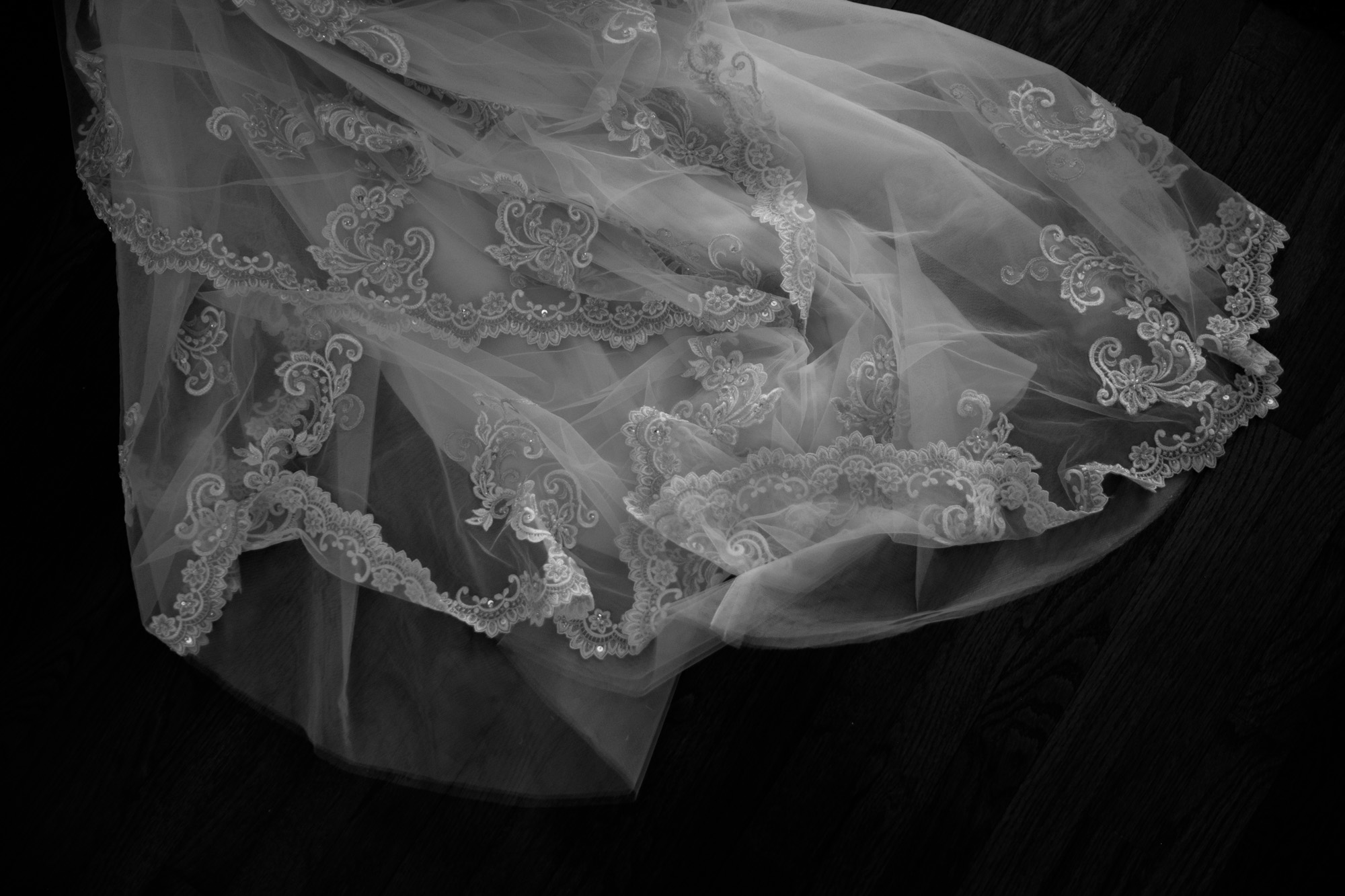 A black and white detail photograph of the brides wedding dress before the ceremony at Whistle Bear in Cambridge.