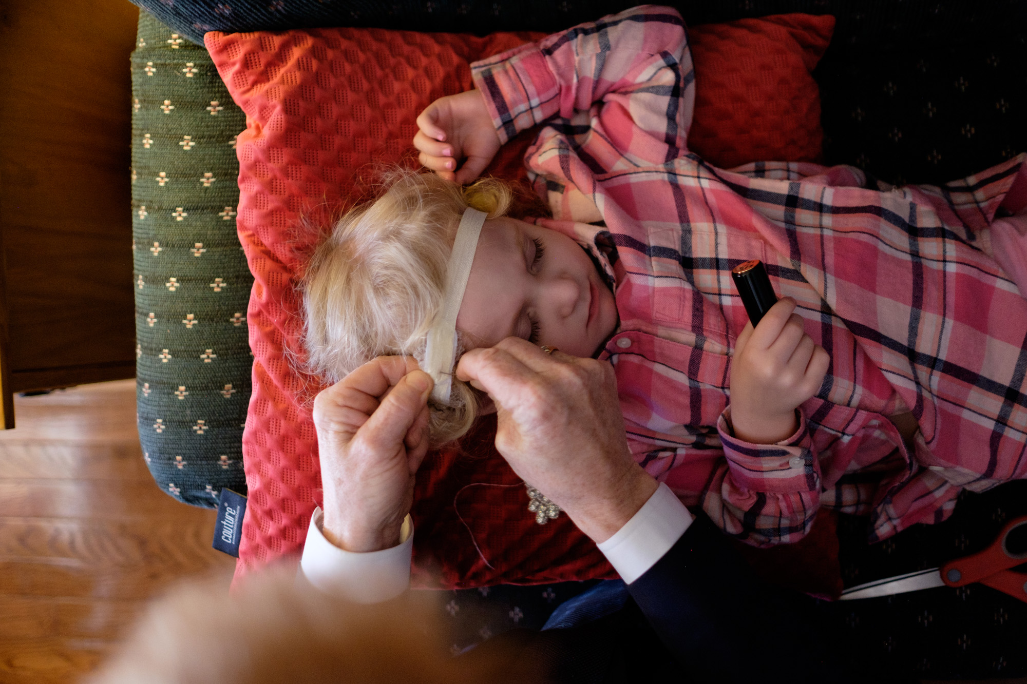 The father of the bride repairs a headpiece for the flower girl before the wedding ceremony at Whistle Bear in Cambridge.