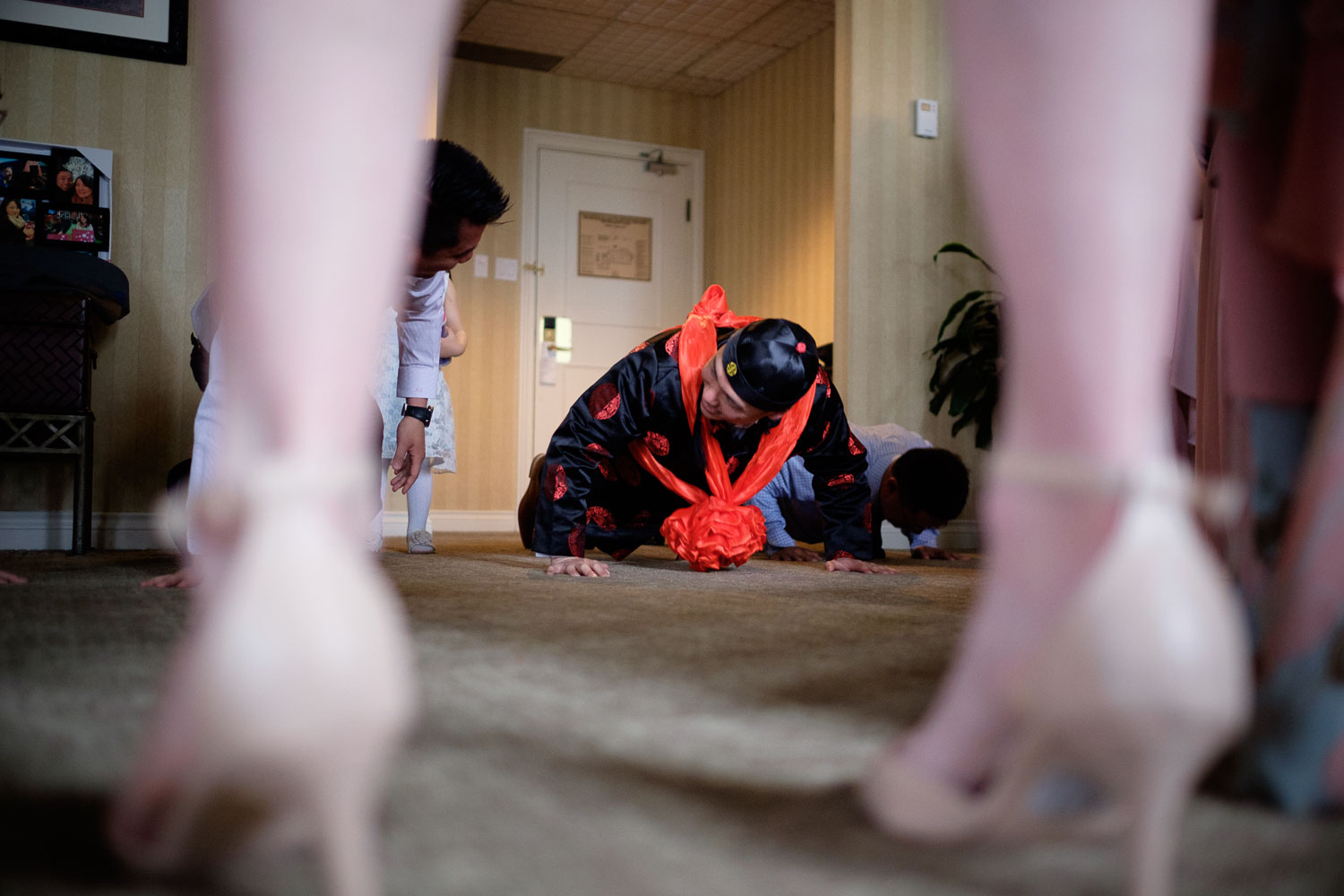 Nelson does some pushups during the door games before the chinese tea ceremony during their wedding at the Guild Inn Estate in  Toronto.