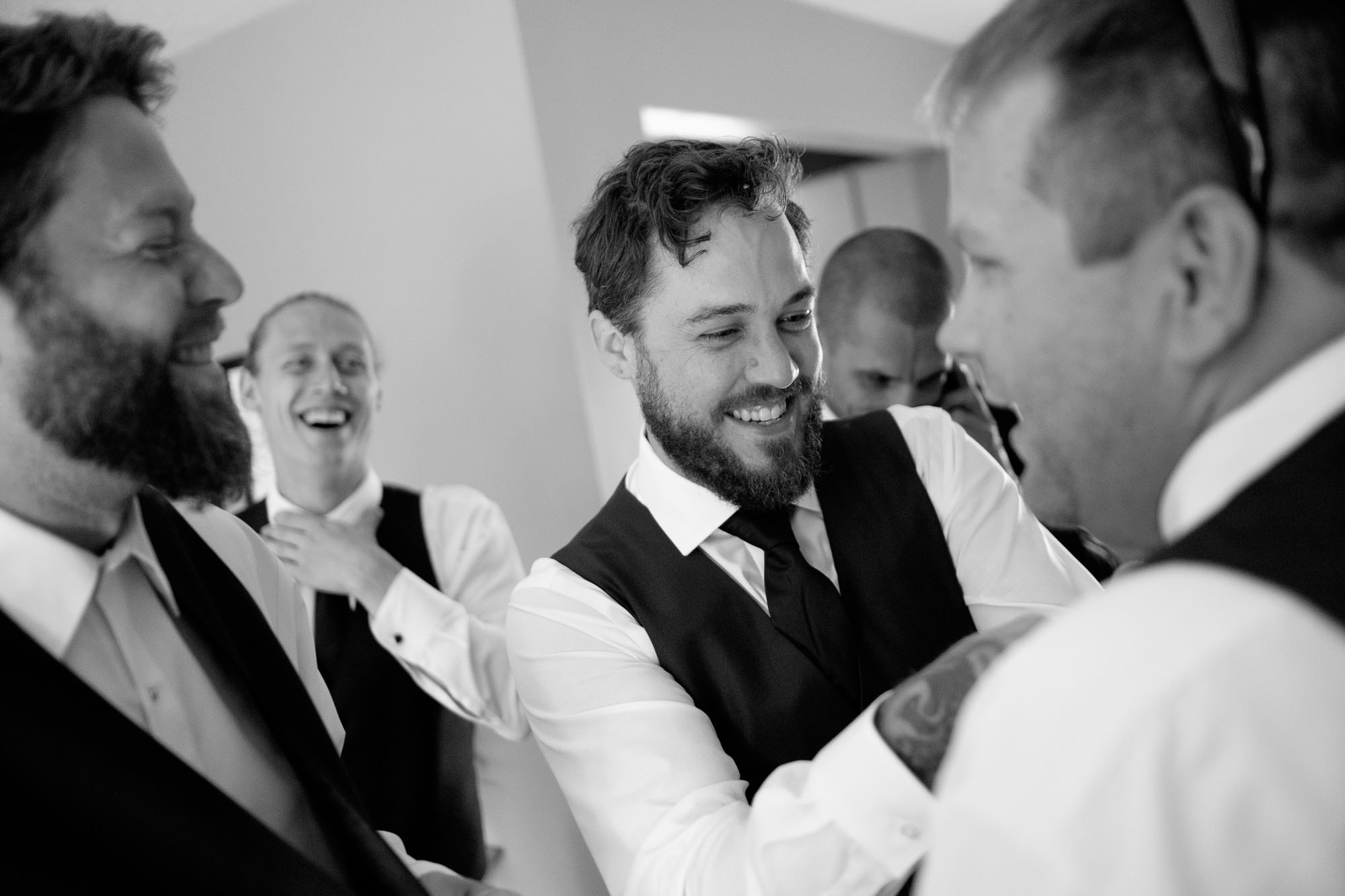 Adam adjusts the tie on one of his groomsmen as they all get ready for his backyard wedding in Ontario, Canada. By Scott Williams.