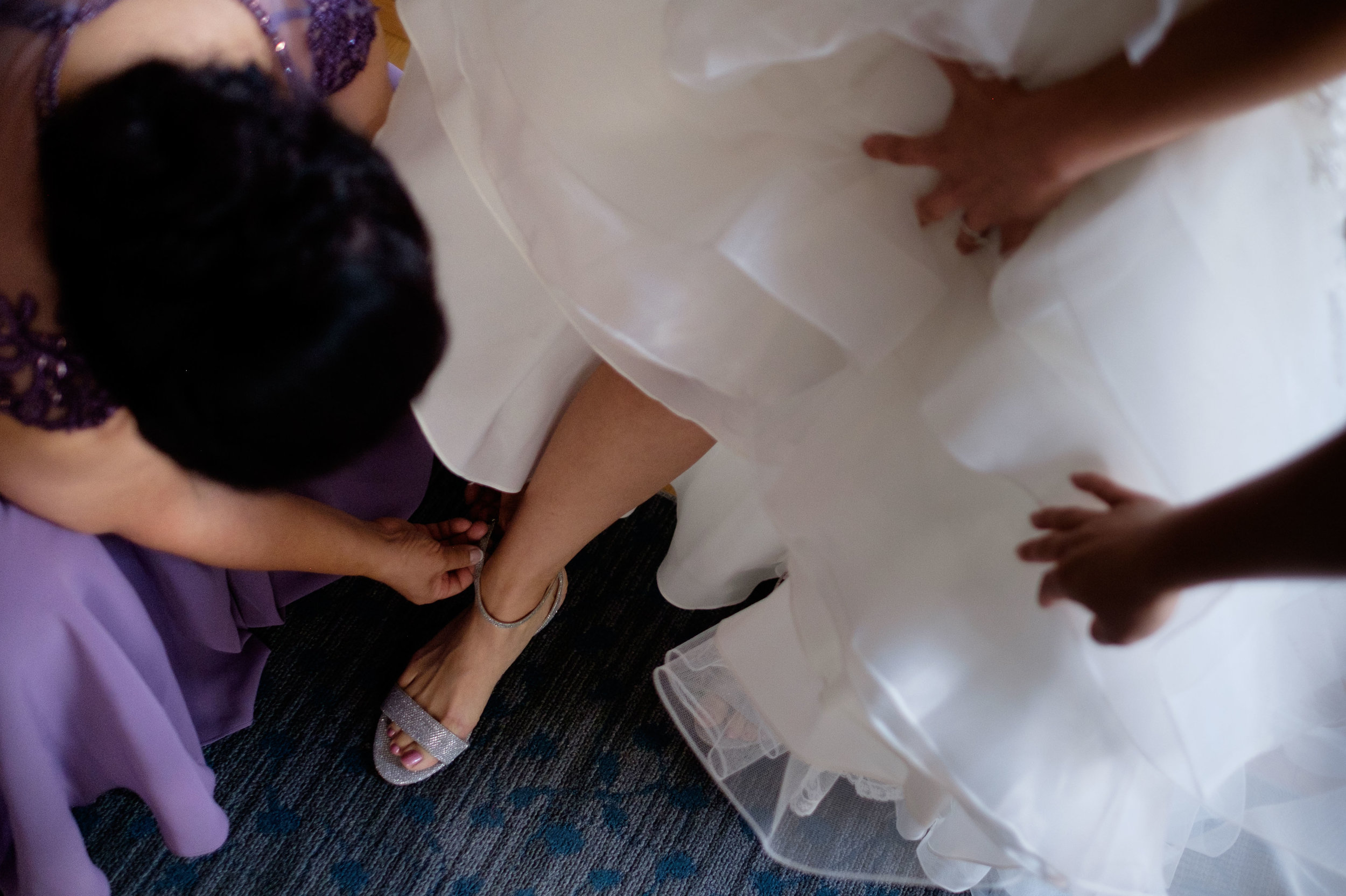Linda gets help with her shoes as she gets ready for her wedding at the Hart House in Toronto.