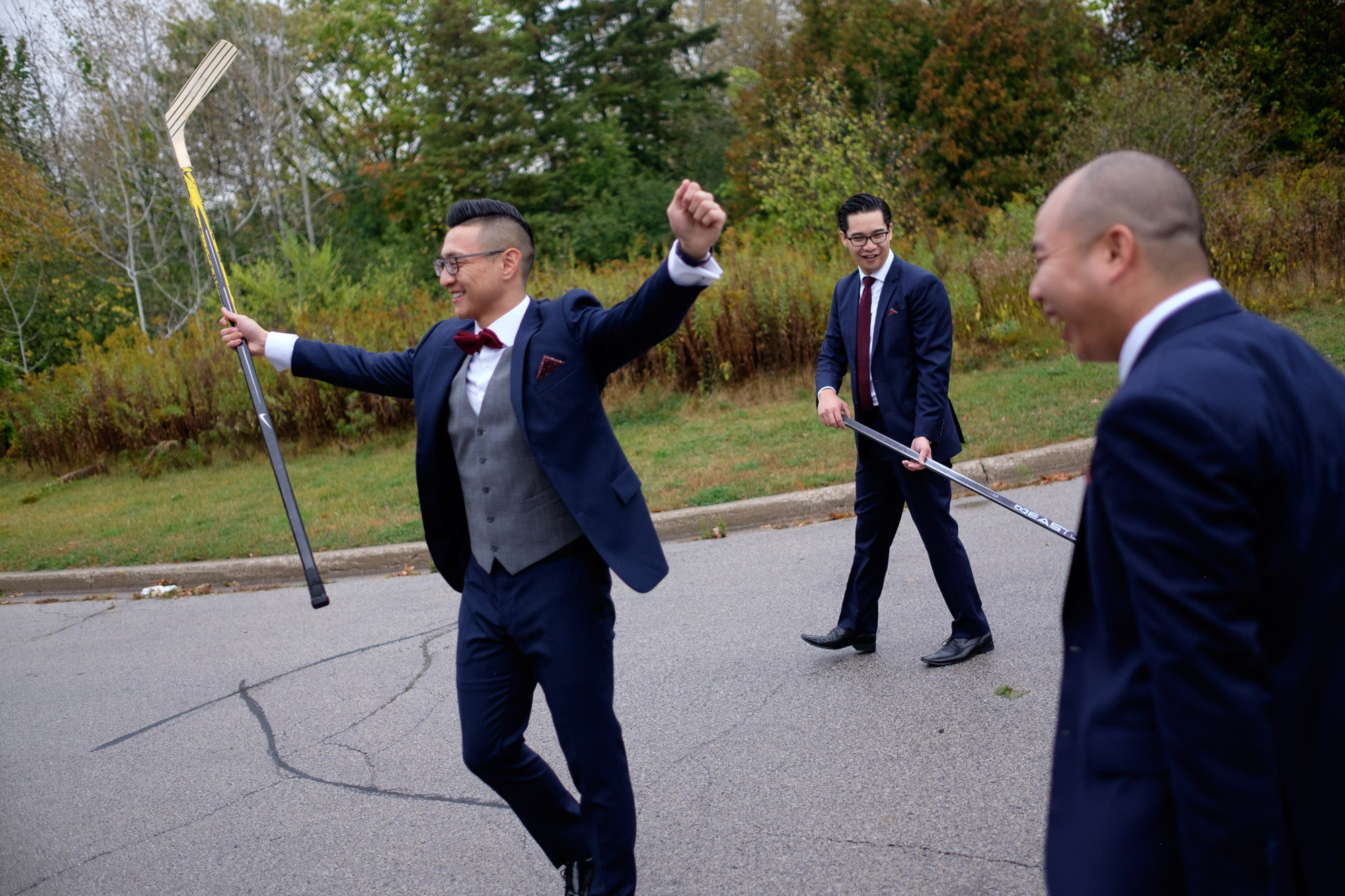 Chris plays road hockey with his groomsmen before his wedding at Madsens Greenhouse.