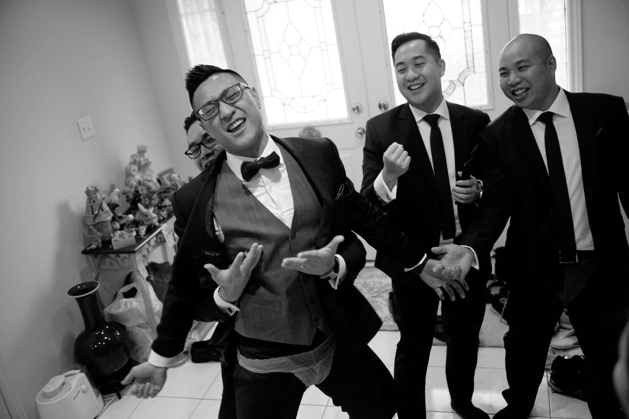 Chris and his groomsmen sing during traditional Chinese door games before their wedding at Madsen's Greenhouse.