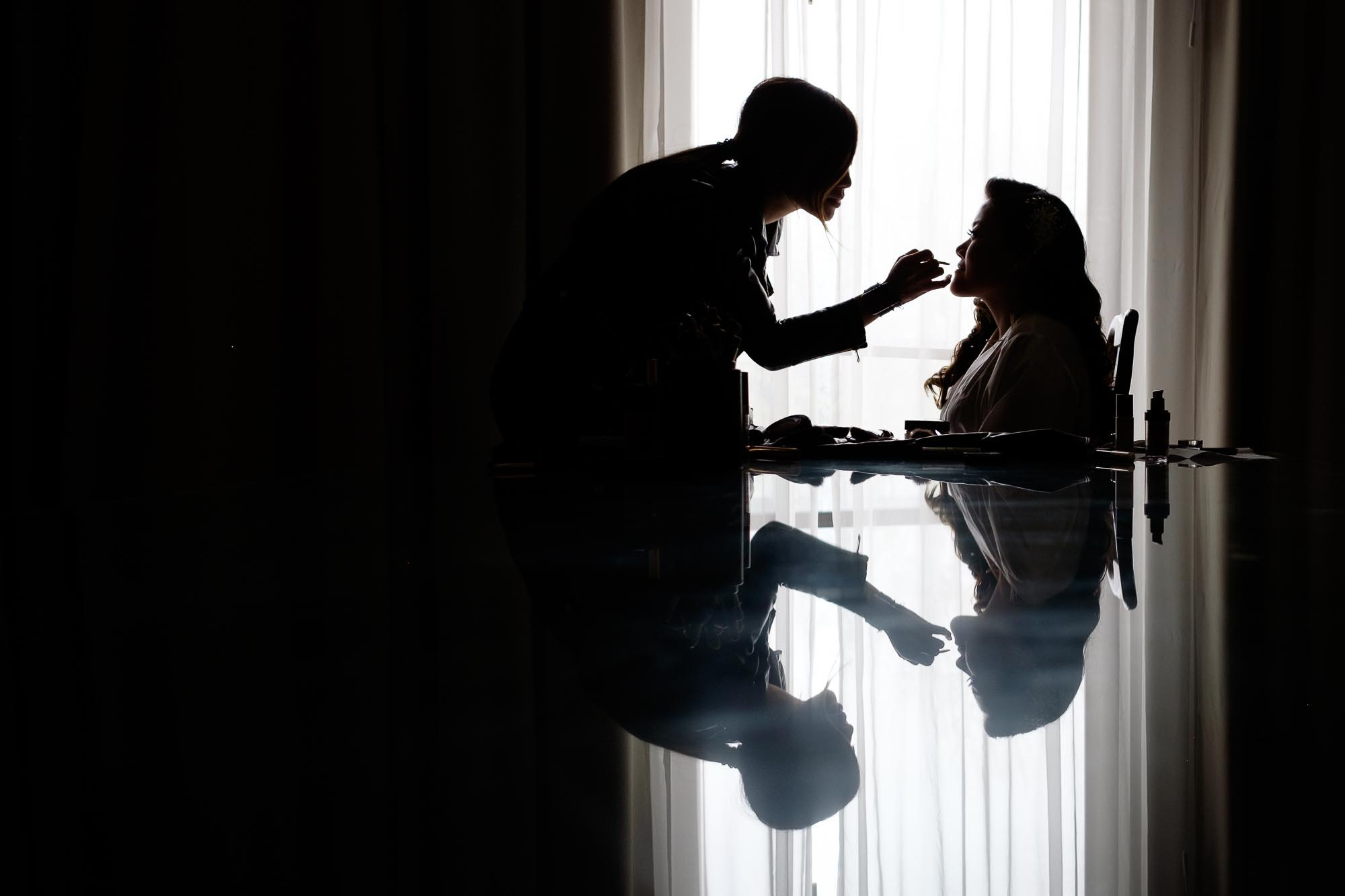 the bride has her makeup applied in her hotel suite before their wedding at the Guild Inn Estate in Toronto, Ontario.