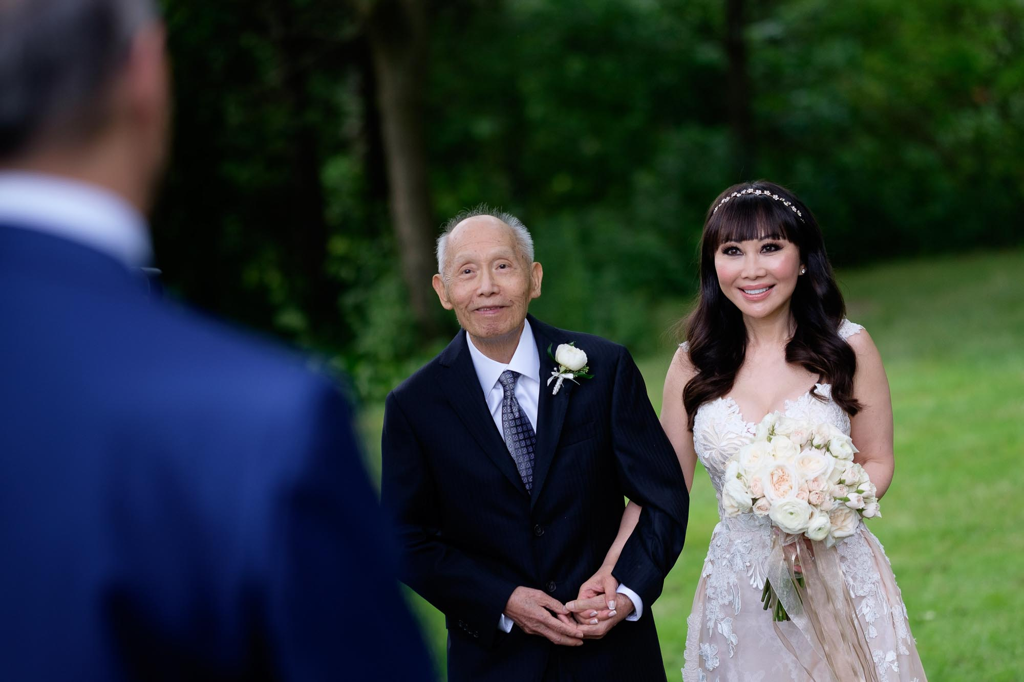 the bride is escorted down the aisle by her father during their outdoor wedding ceremony at Langdon Hall in Cambridge, Ontario.