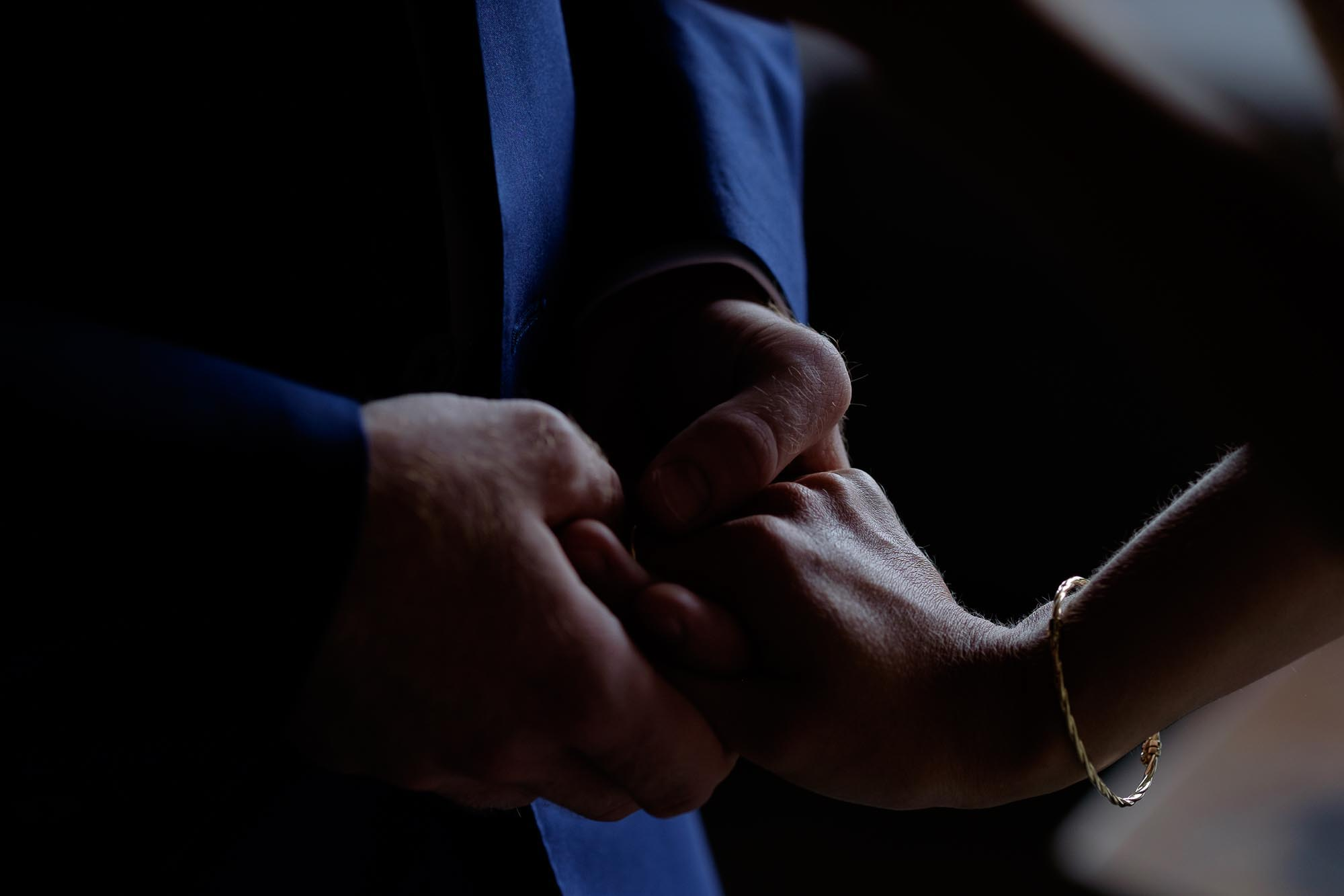 the bride and grooms hands embrace during the wedding ceremony.