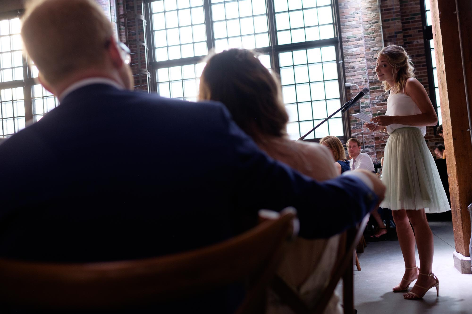 the bride and groom listen to a speech during  a wedding reception at SteamWhistle Brewery in Toronto.