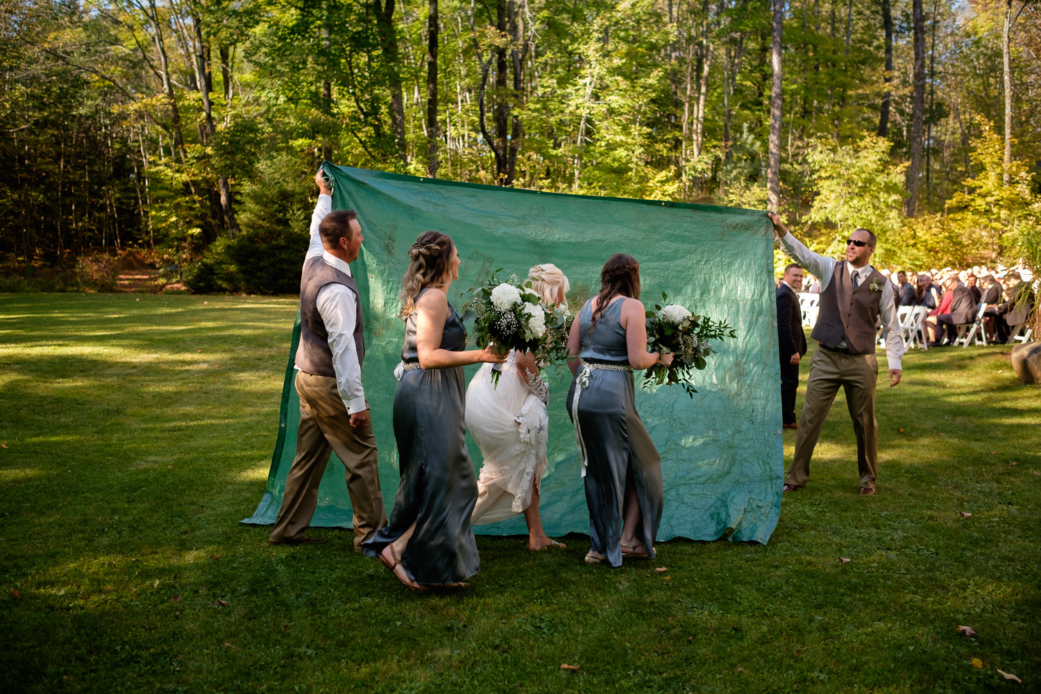 A bride sneaks past her wedding guests before her backyard outdoor wedding ceremony at their private residence in Muskoka, Ontario by Toronto wedding photographer Scott Williams.