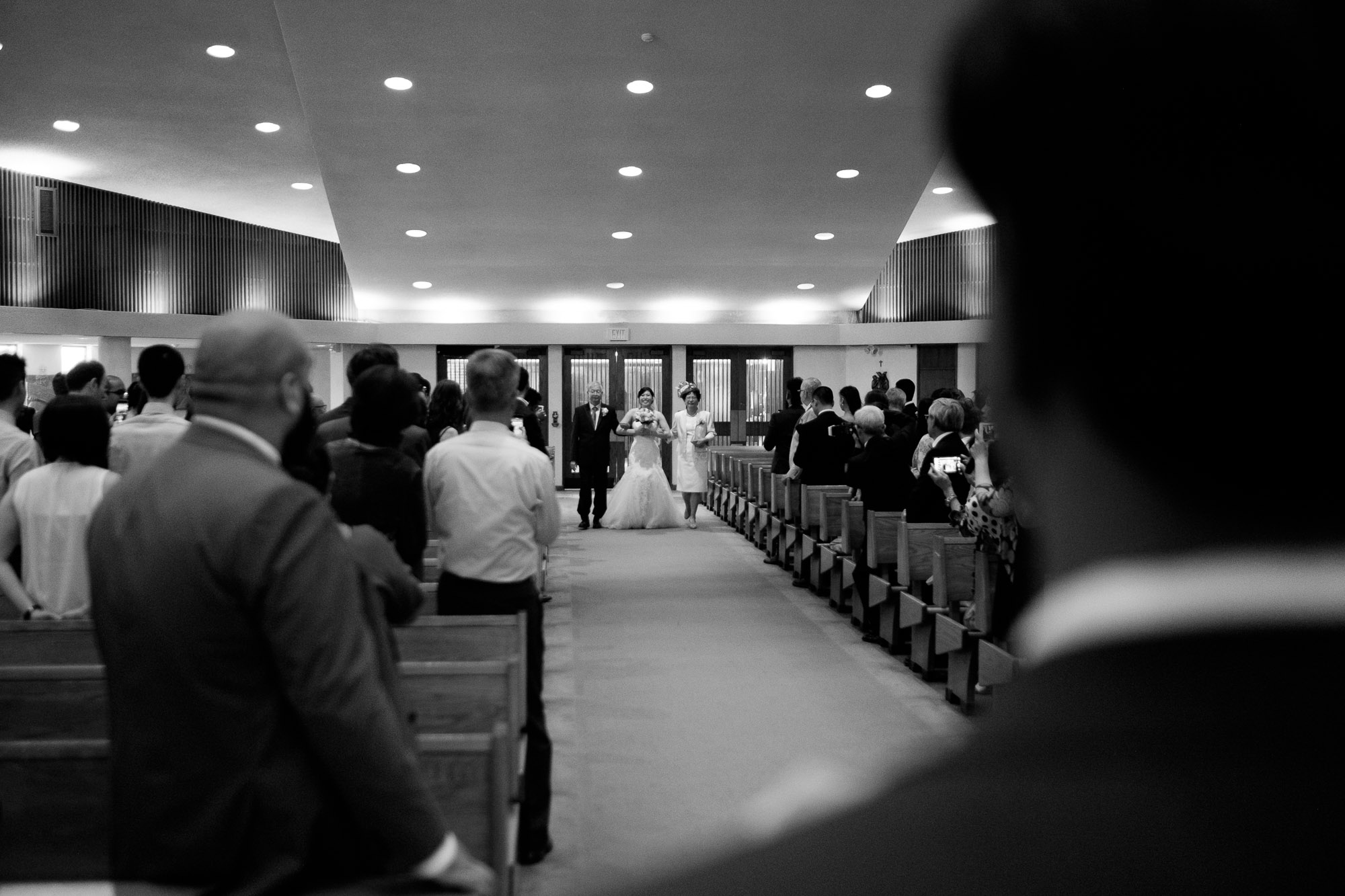 The groom sees his bride walking down the aisle for the first time during their Roman Catholic wedding ceremony in Toronto.