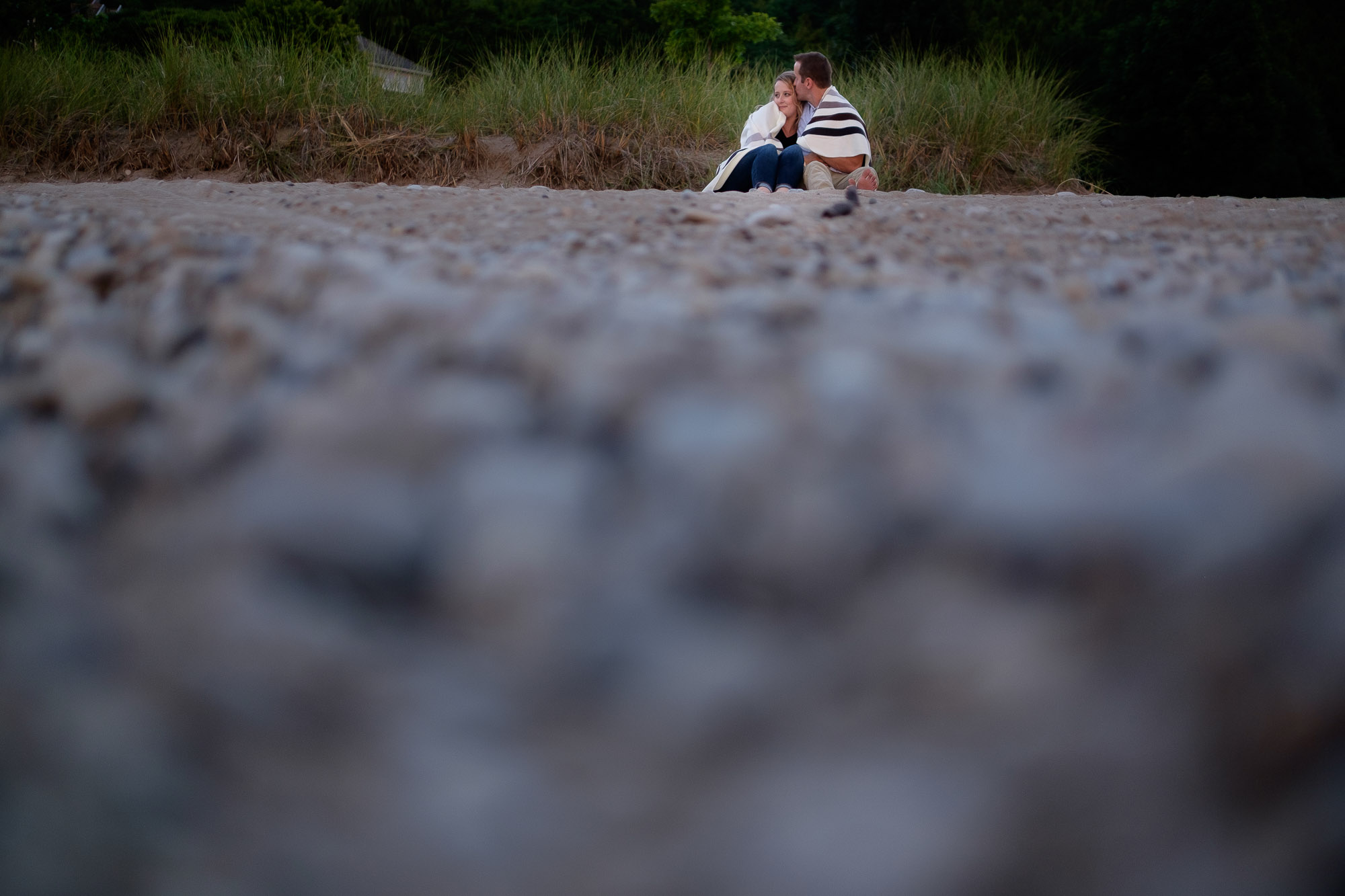 Alex + Colton stay warm under a blanket on a rocky beach during their Goderich engagement shoot.